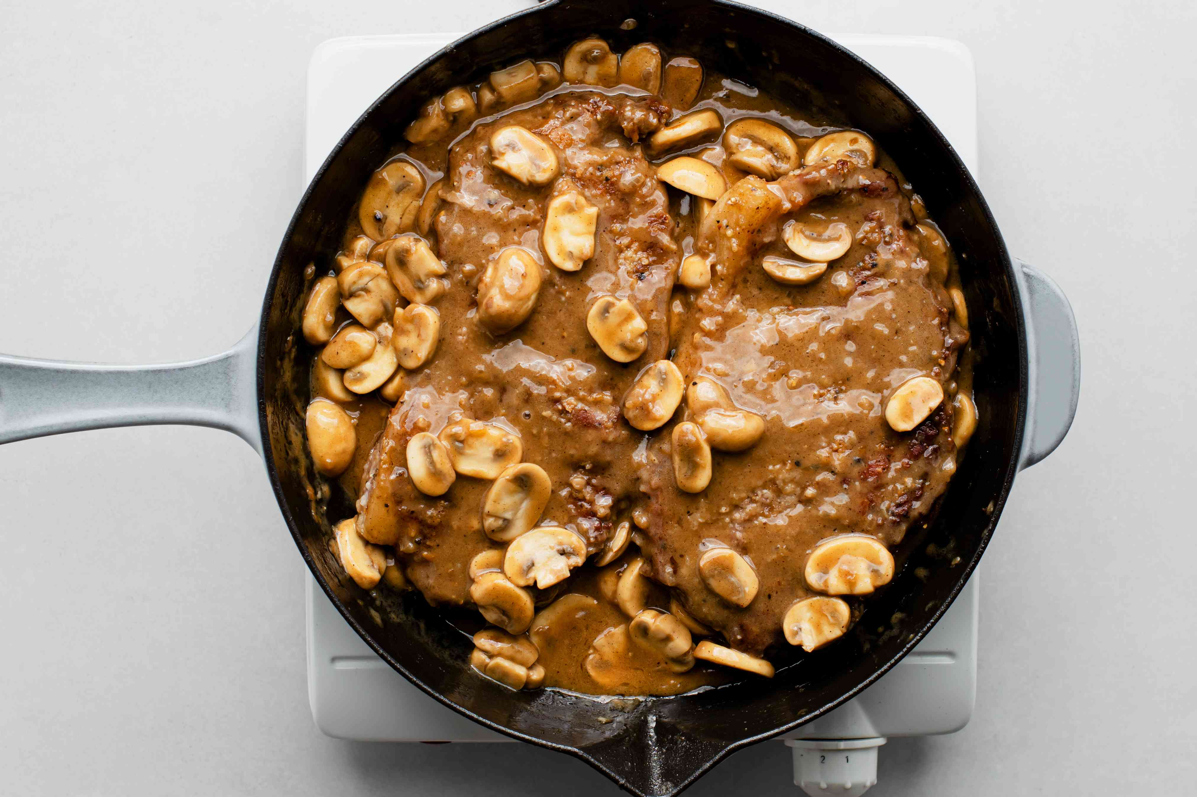 steaks cooking together with the Marsala mushroom sauce