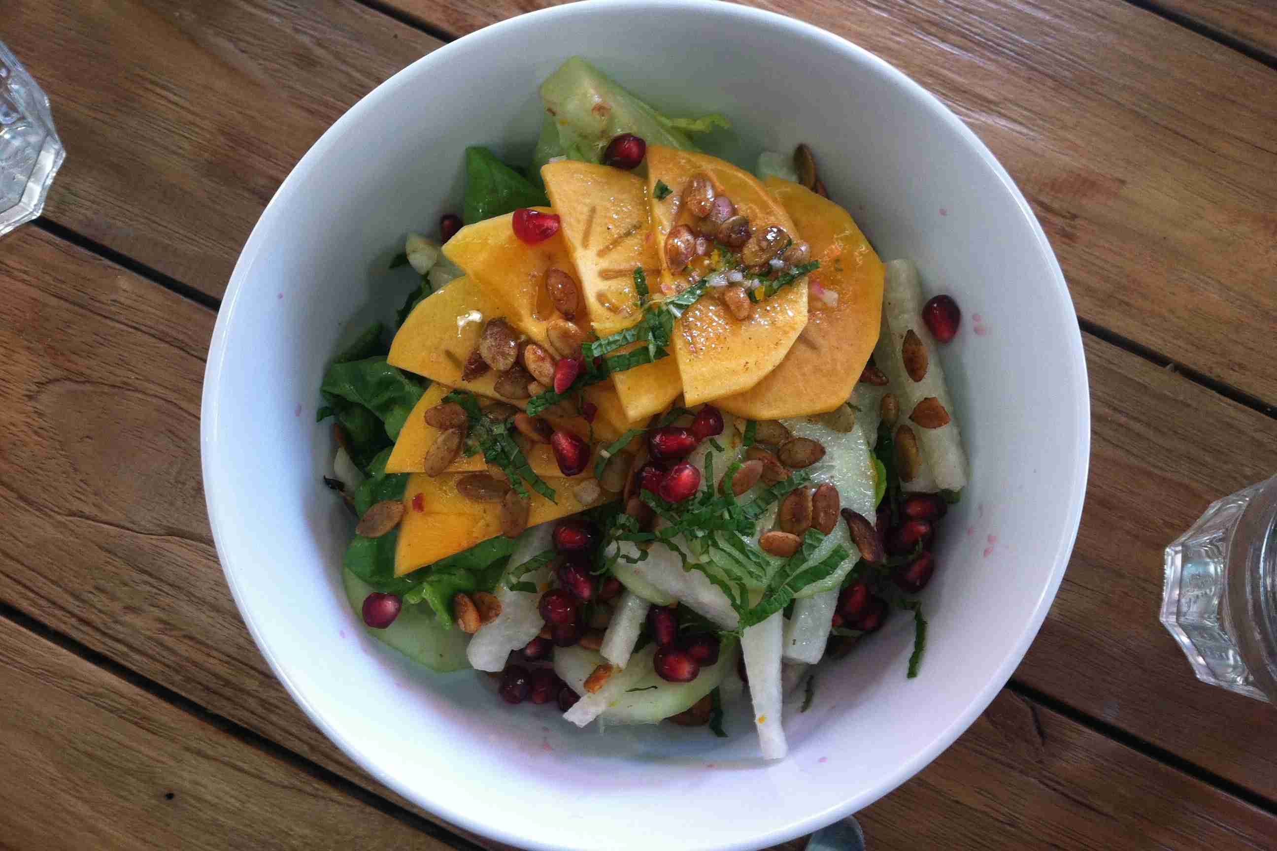 A bowl of pomegranate seeds on autumn salad