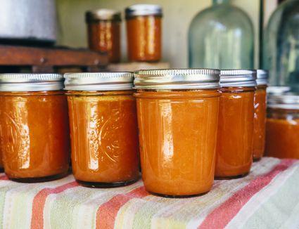 Jars of peach jam on table