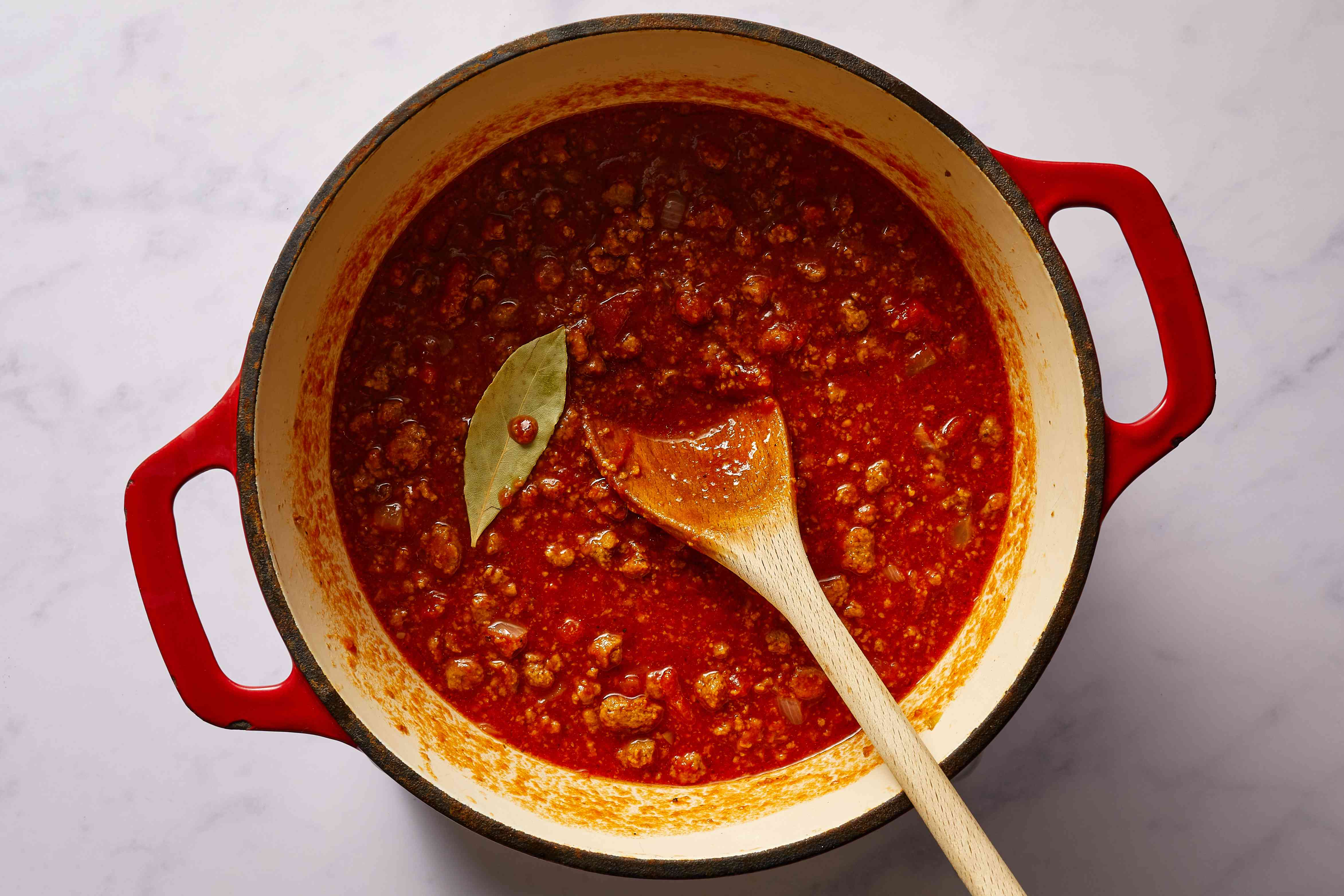 meat and tomato sauce with bay leaf in a pot
