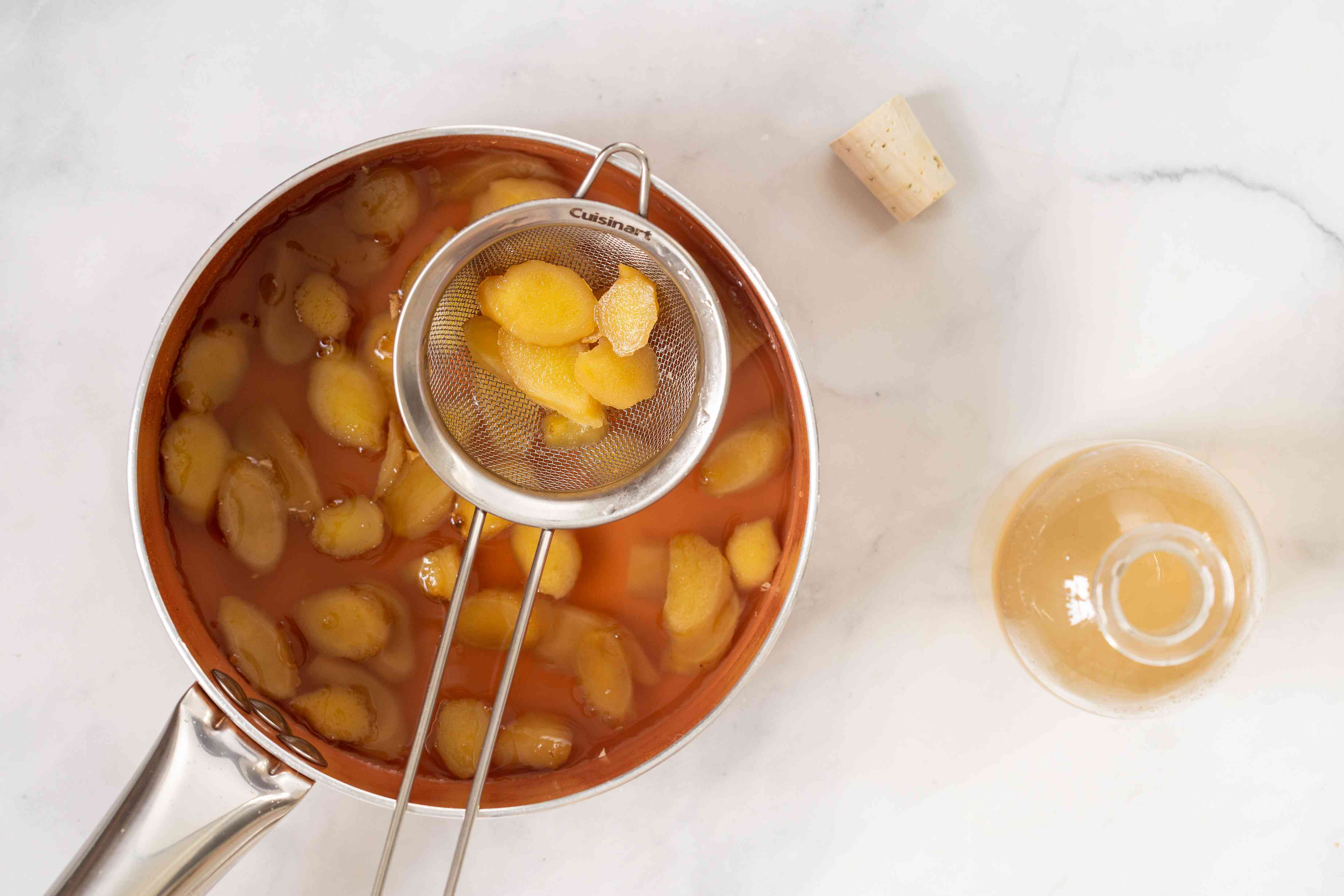 Straining out ginger from the simple syrup in a pot