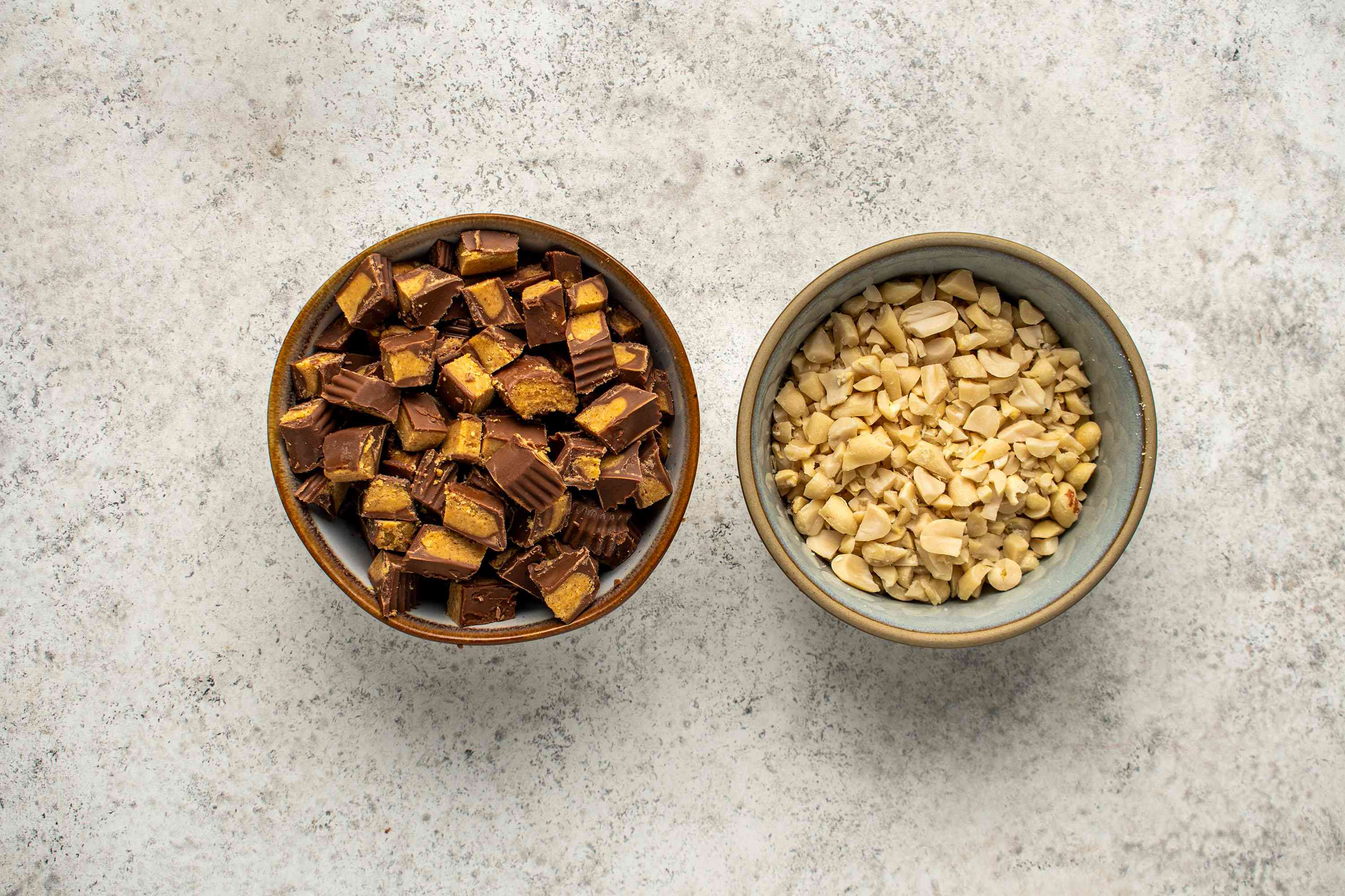 Place the chopped peanut butter cups and peanuts in separate bowls