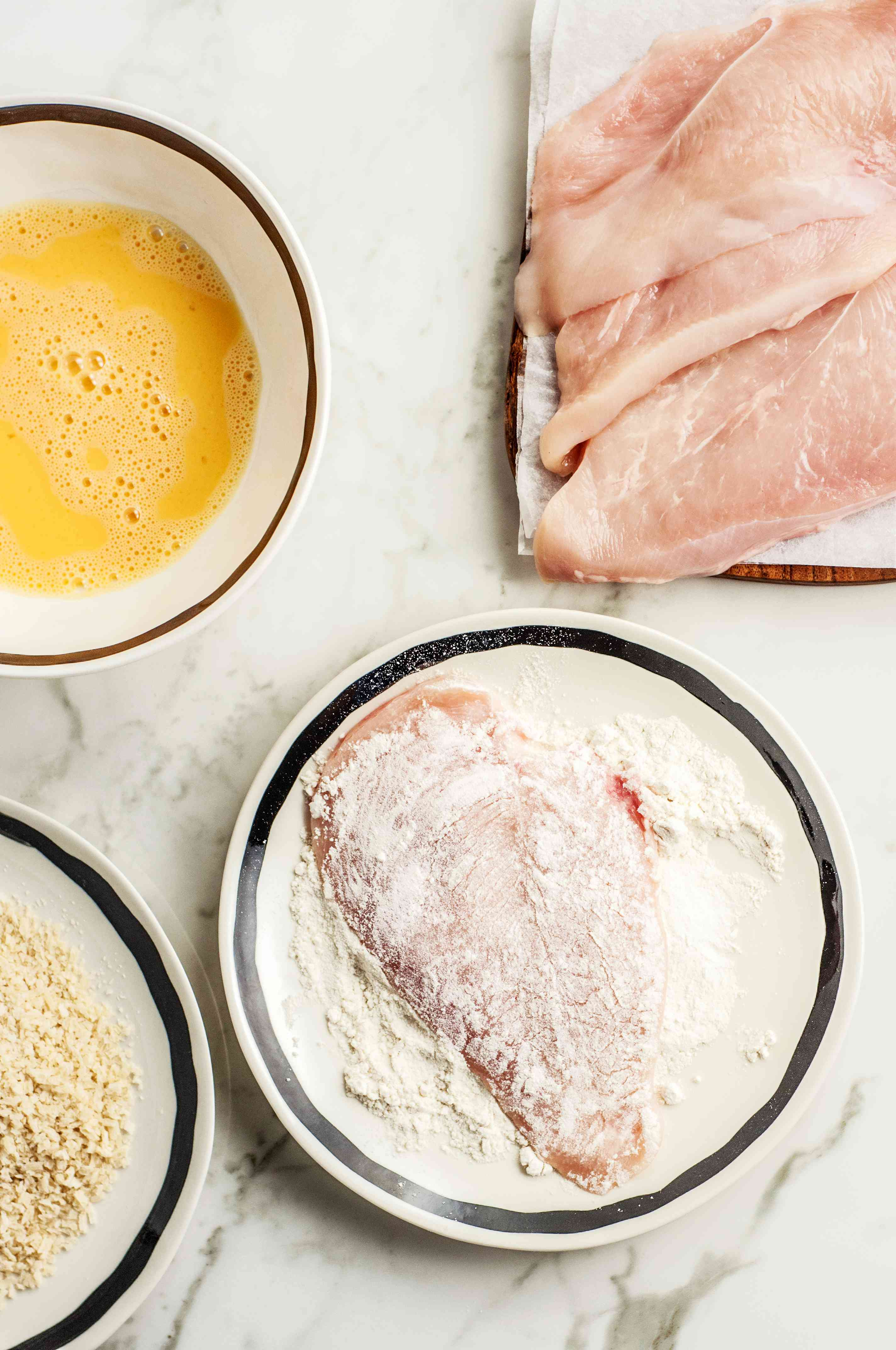 Dredging chicken breasts in egg, flour and breadcrumbs