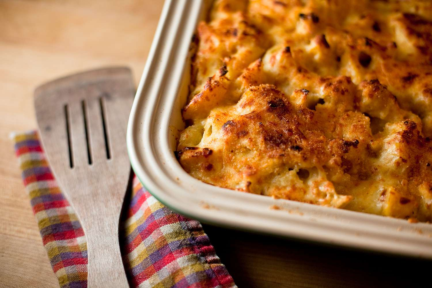 A freshly baked macaroni and cheese dish made with organic acorn squash, along with a wooden spatula for serving