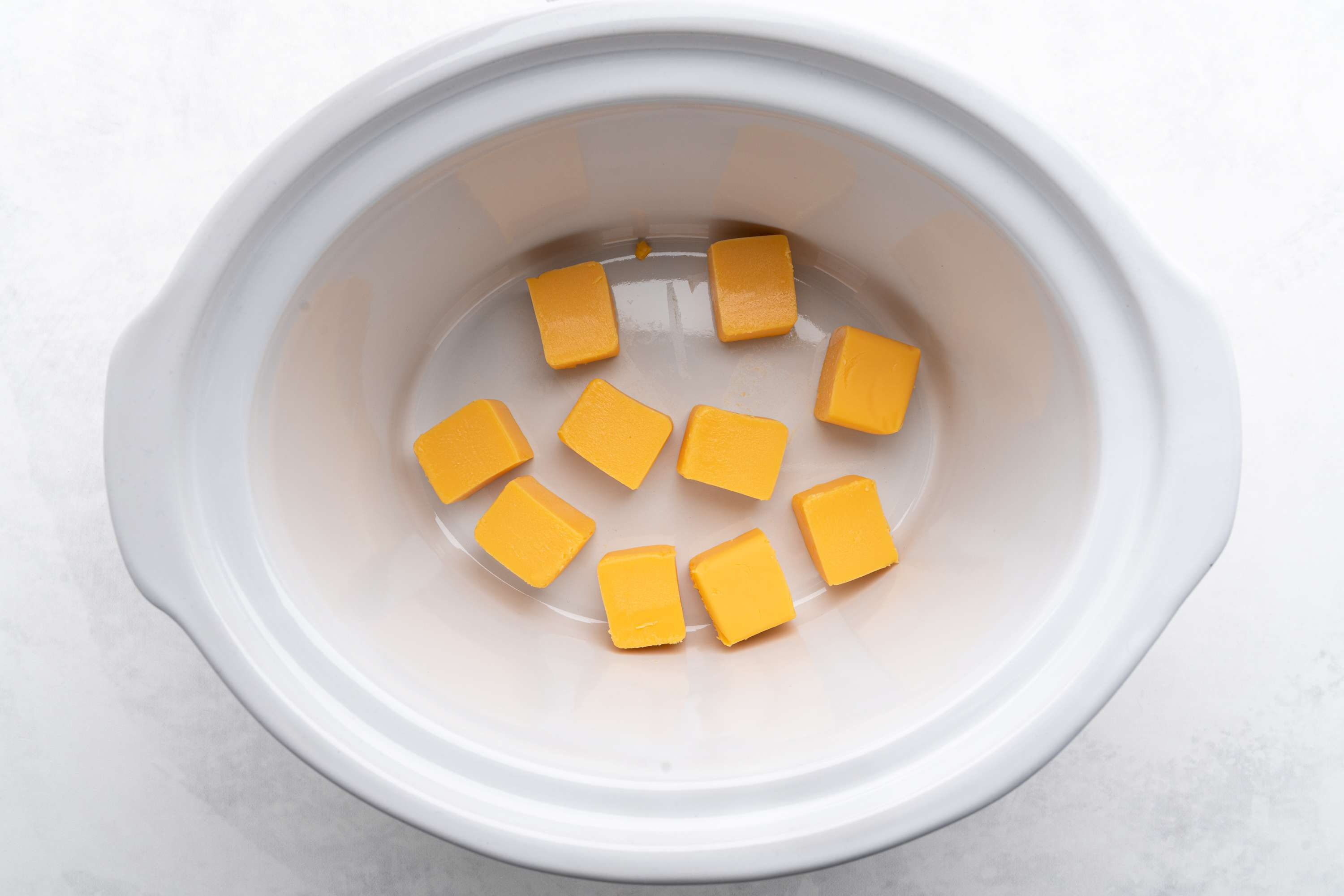 Cube Velveeta cheese and place in slow cooker