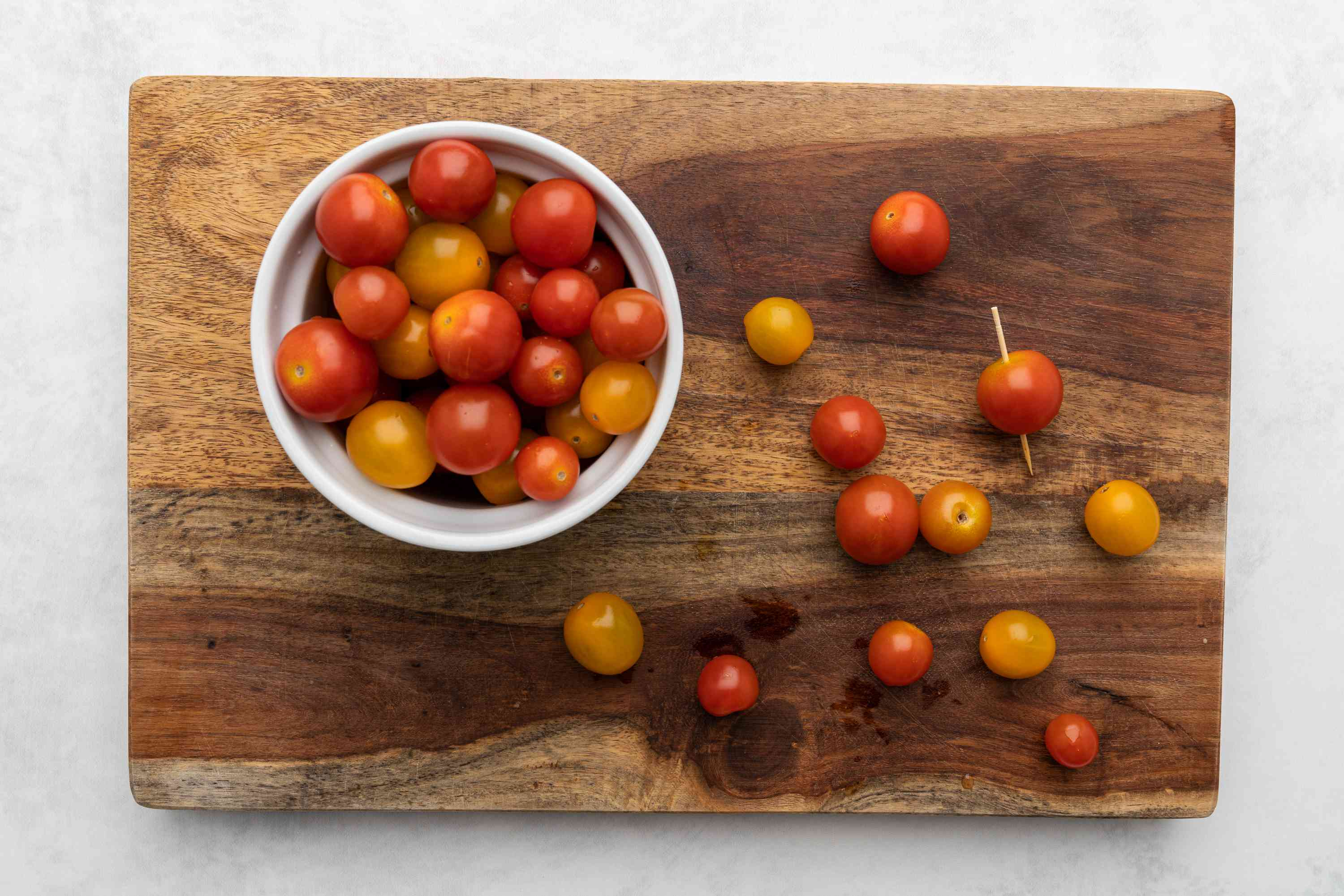 Cherry Tomatoes poked with a toothpick on a cutting board