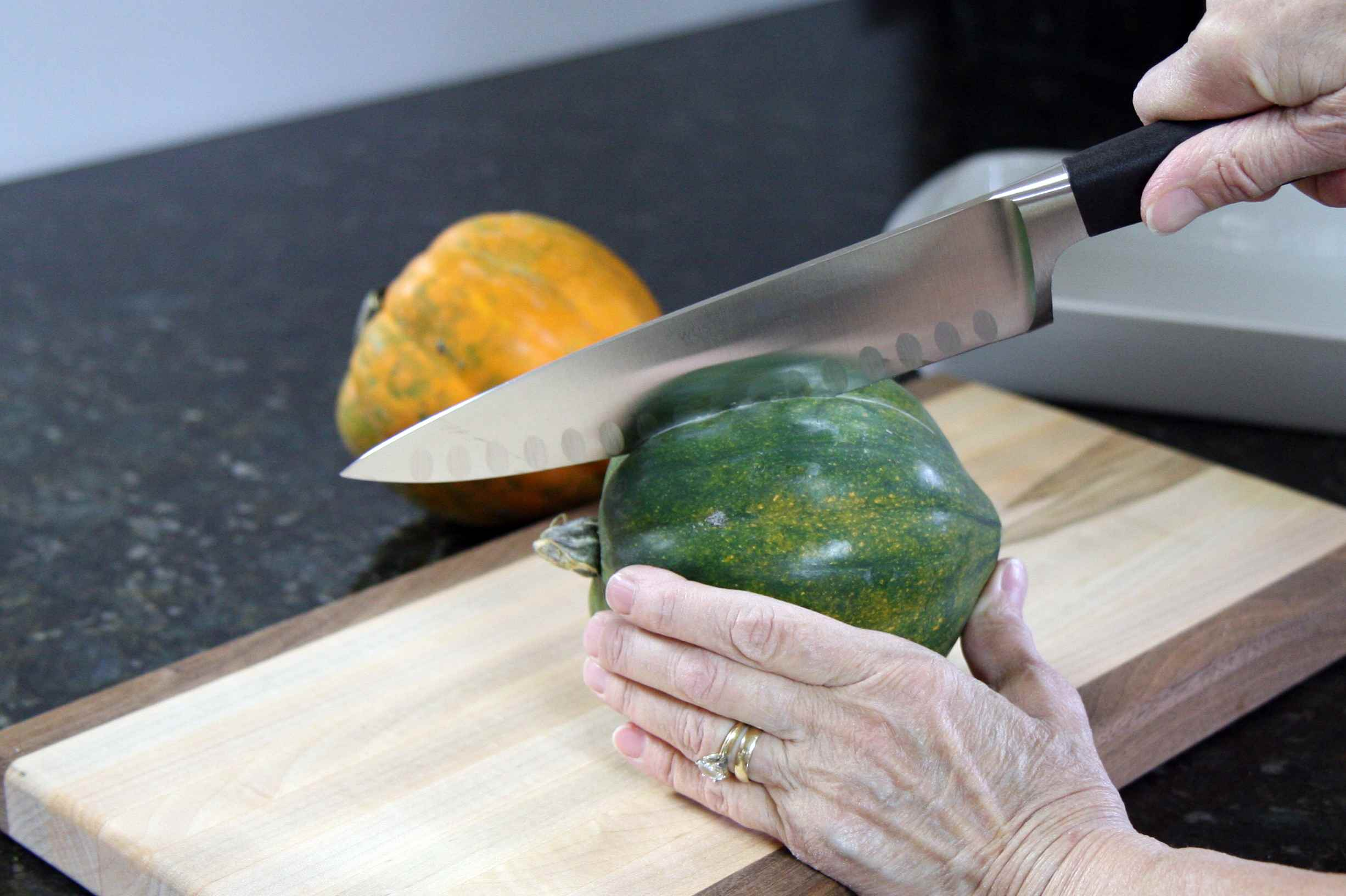 An acorn squash on a cutting board being cut with a chef's knife