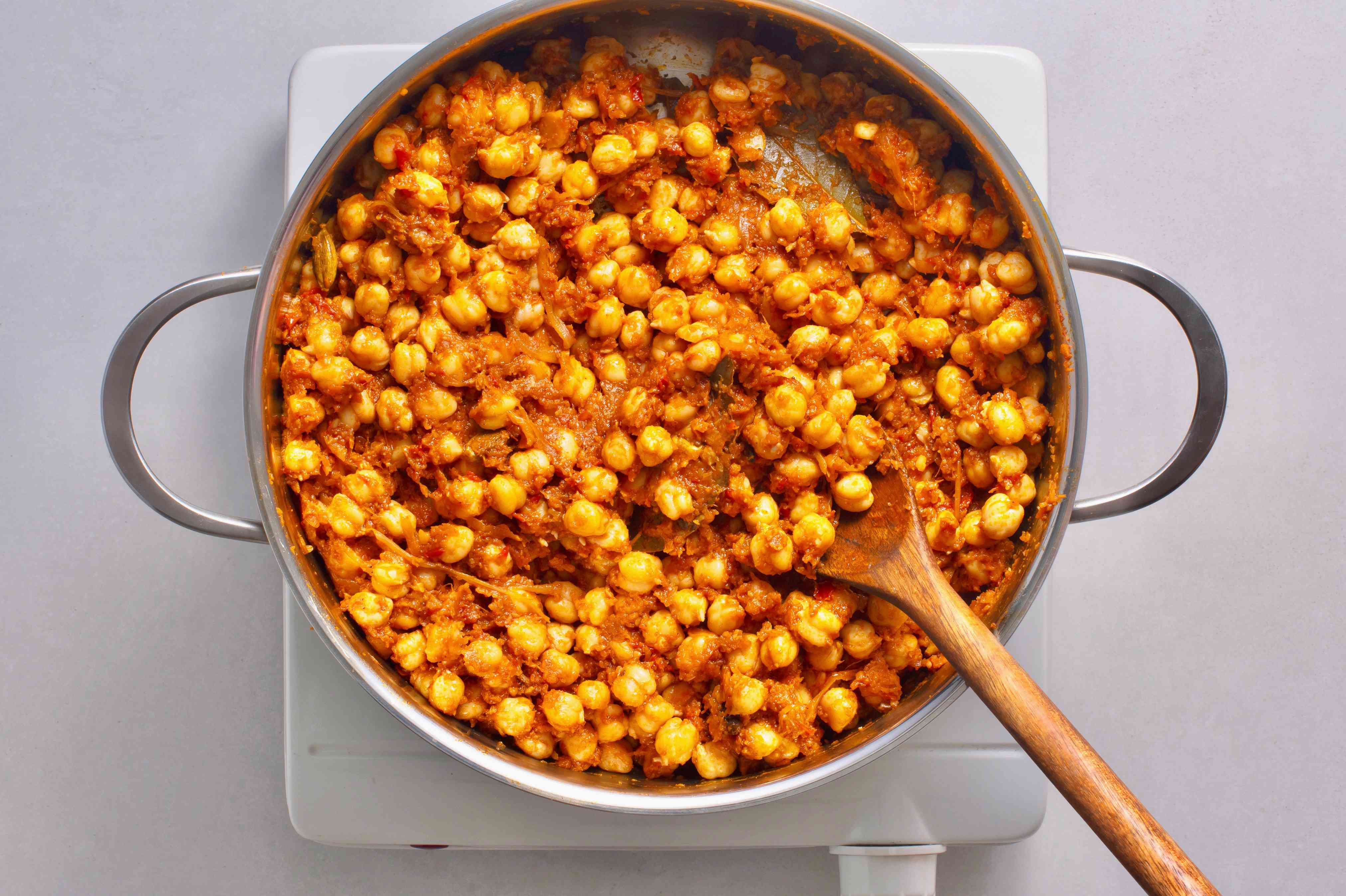 Chickpeas added to masala in the pot