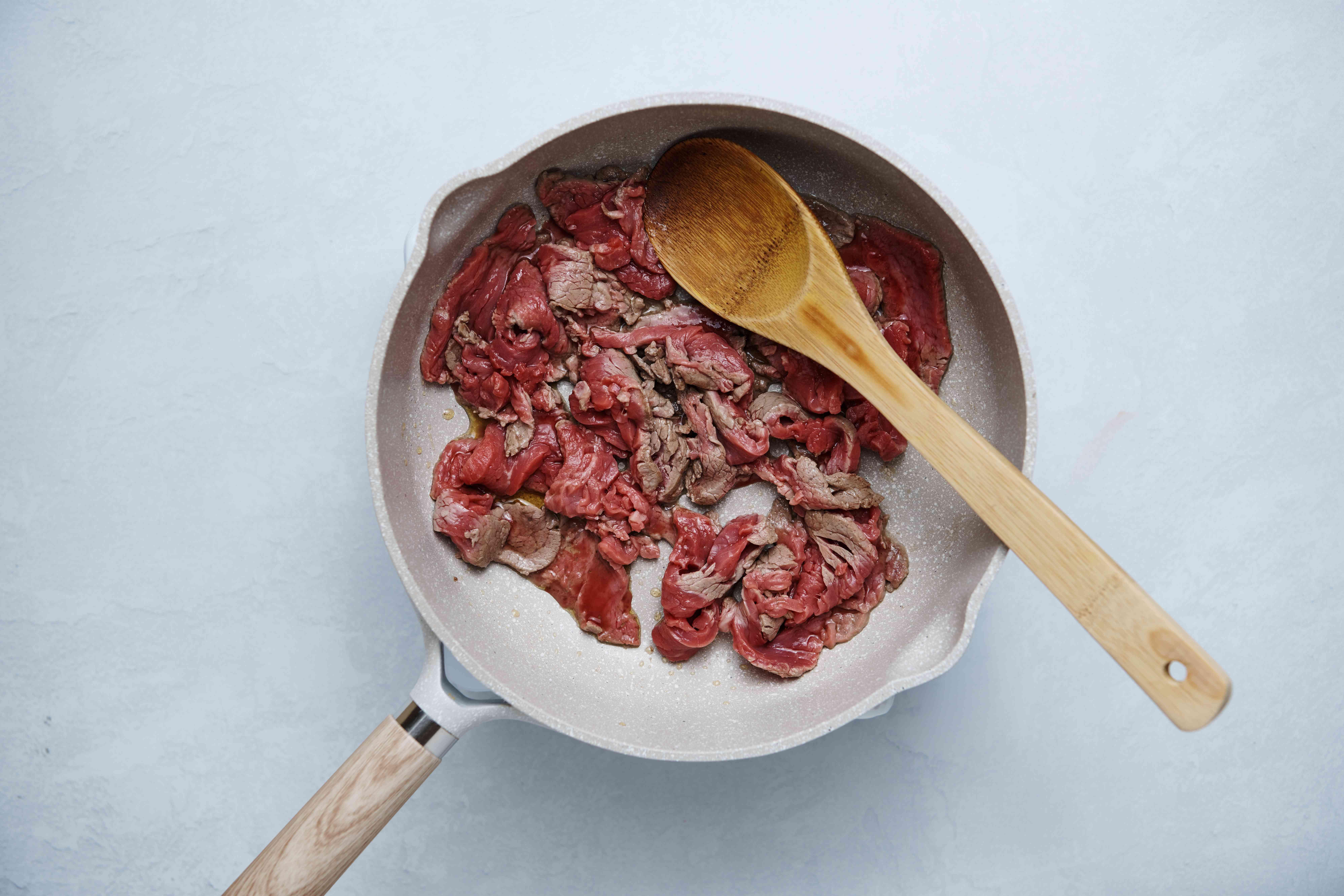 Beef in a pot sautéing in sesame oil