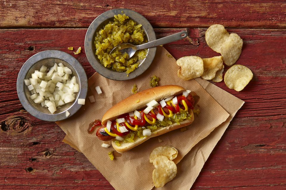 Hot Dog on a brown paper bag with onions, relish and chips