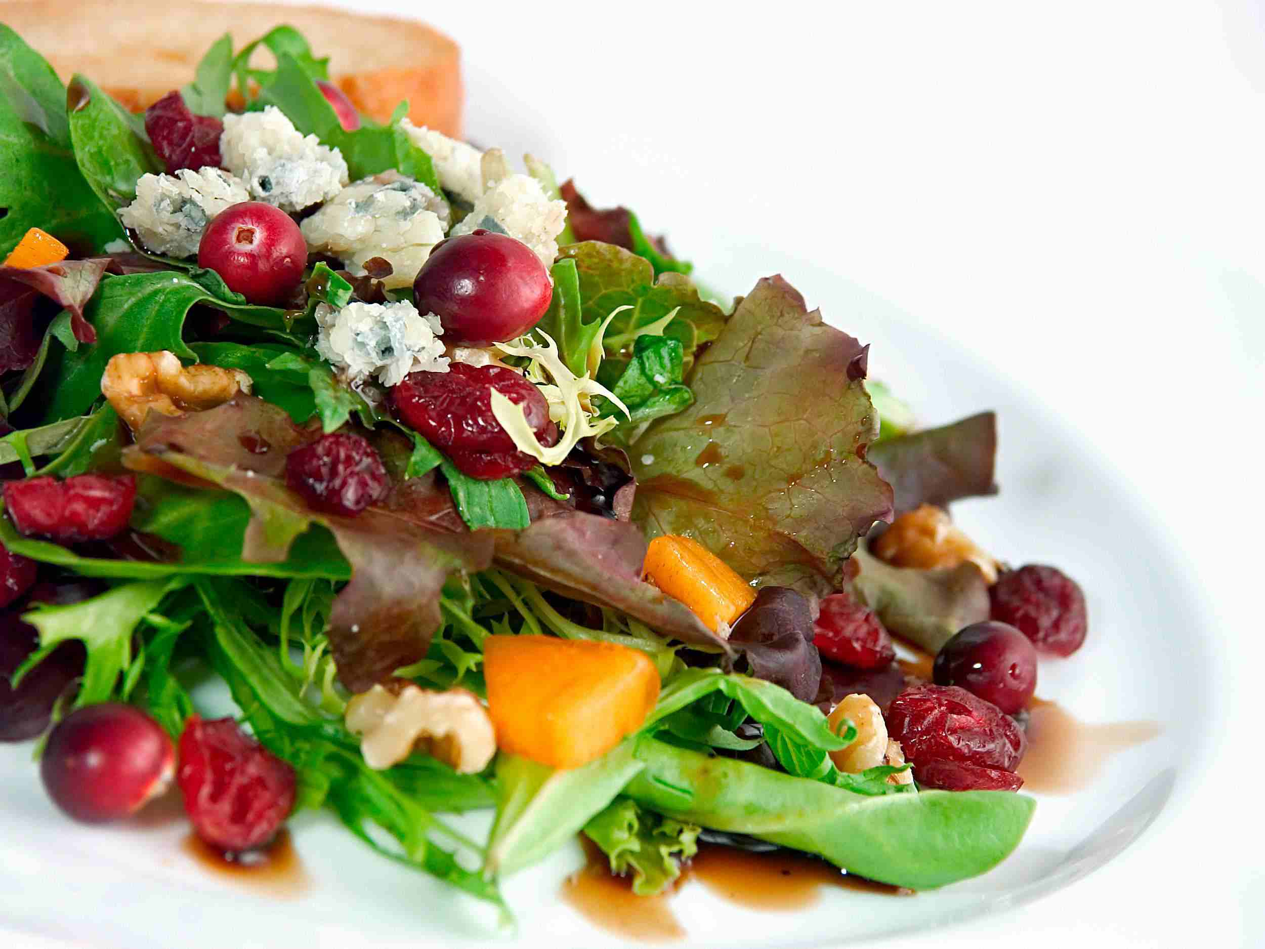 Green salad with dried cranberries and fig balsamic dressing on a plate