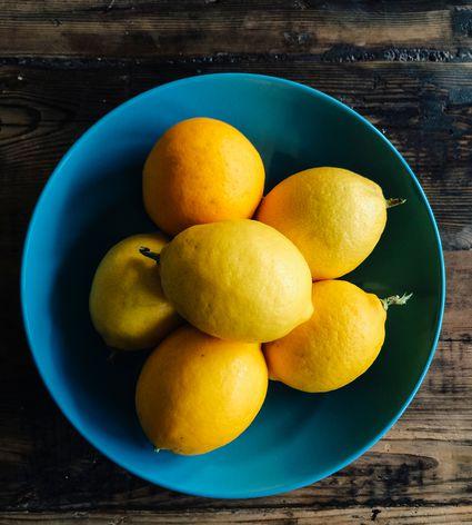 Meyer Lemons In Bowl On Wooden Table