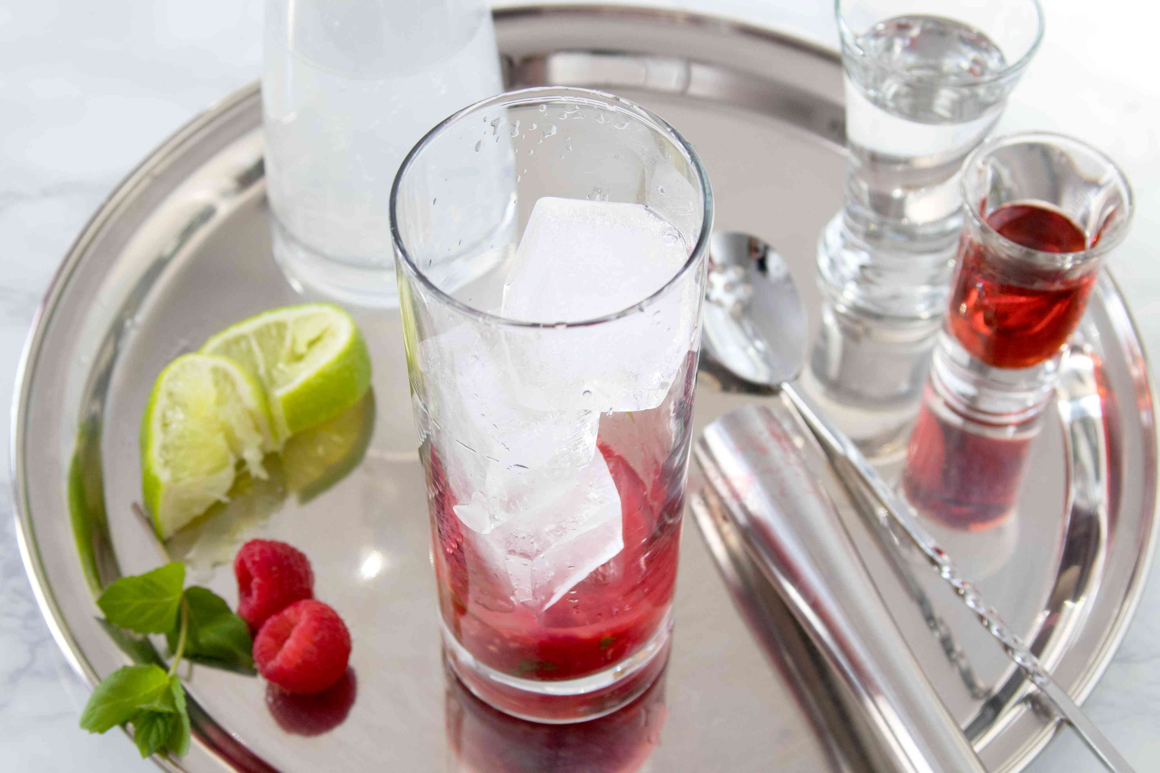 Ice and lime juice added to the glass