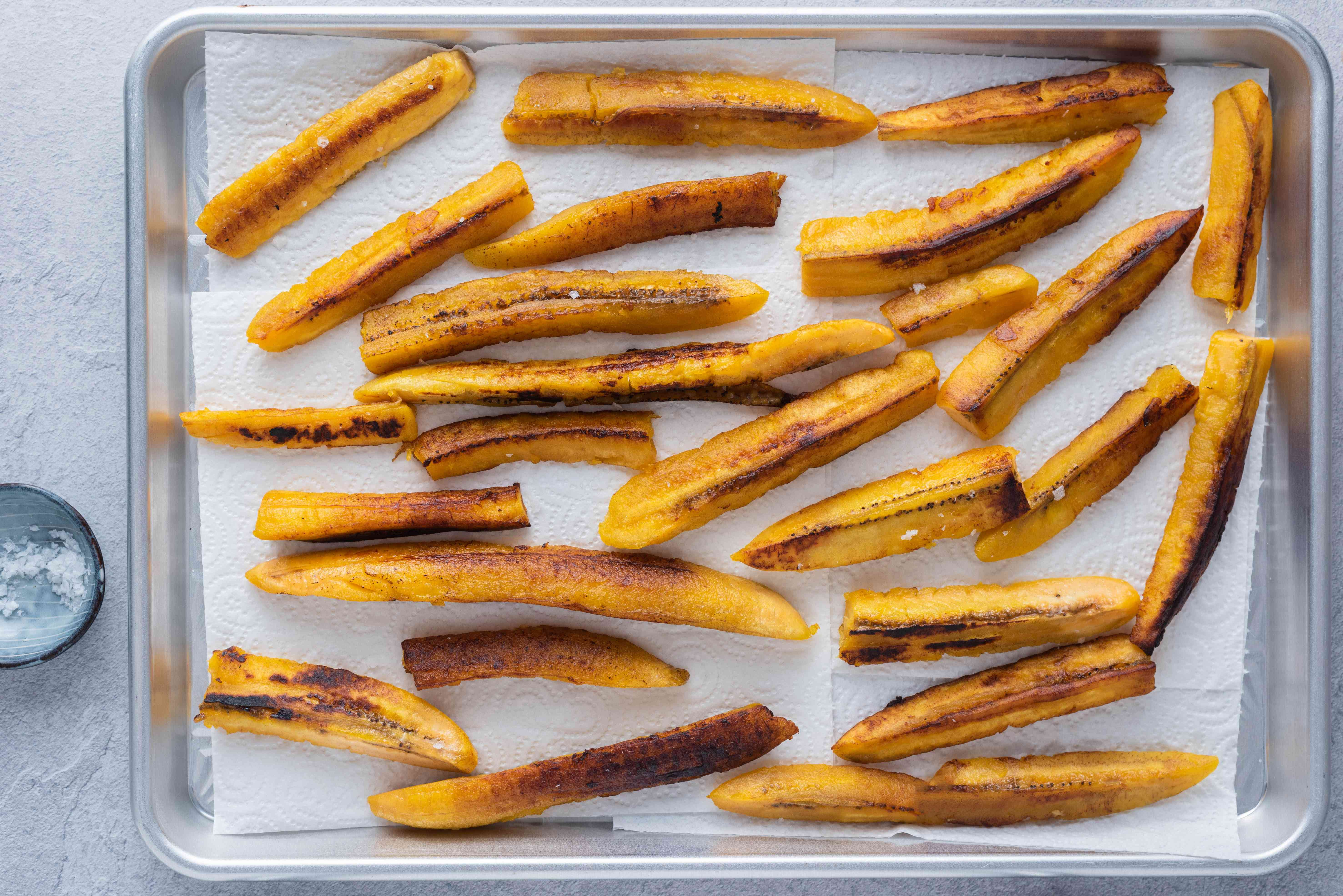 fried plantain pieces on a paper towel lined baking sheet