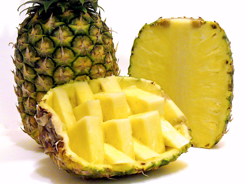 Close up of pineapples, whole and sliced.