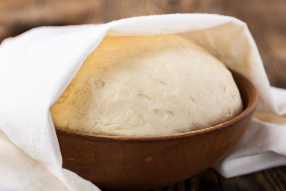 Raw yeast dough in rustic ceramic bowl