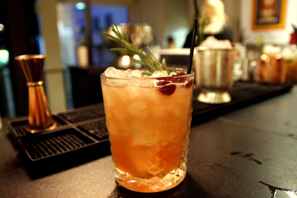 Roy rogers cocktail garnished with cherries and rosemary on a black bar