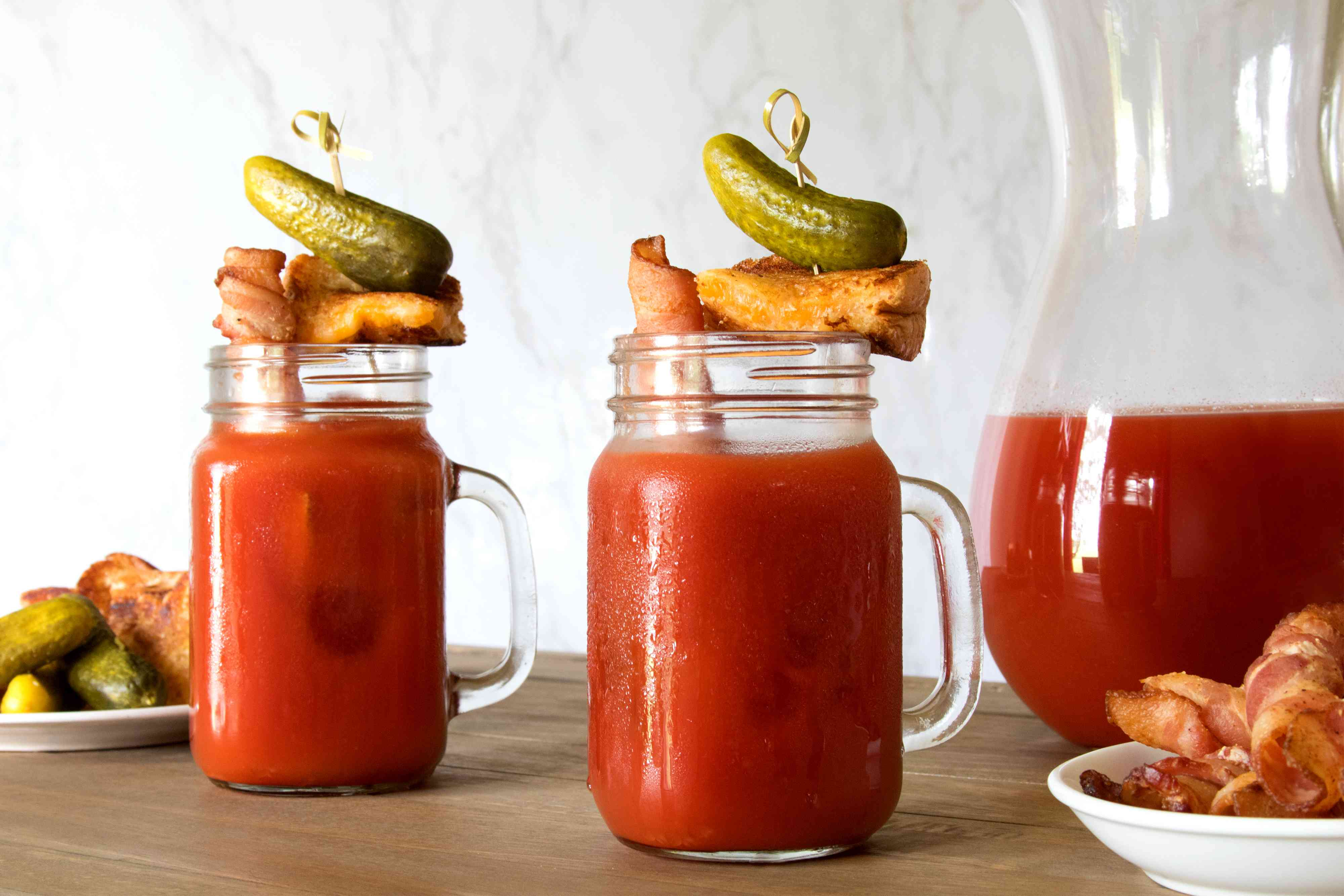 Mugs of crazy bloody mary with bacon straw and grilled cheese
