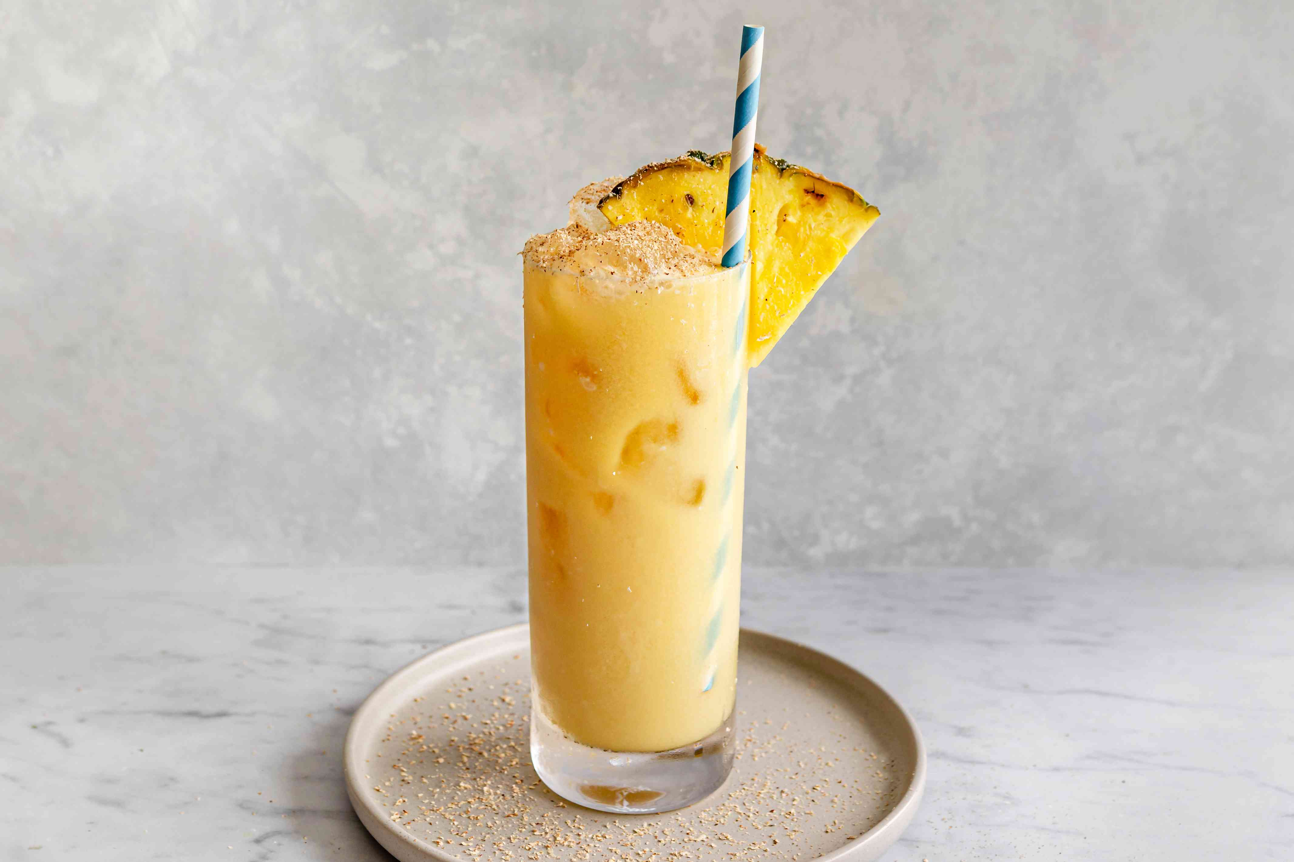 Painkiller cocktail with a straw and a wedge of fresh pineapple