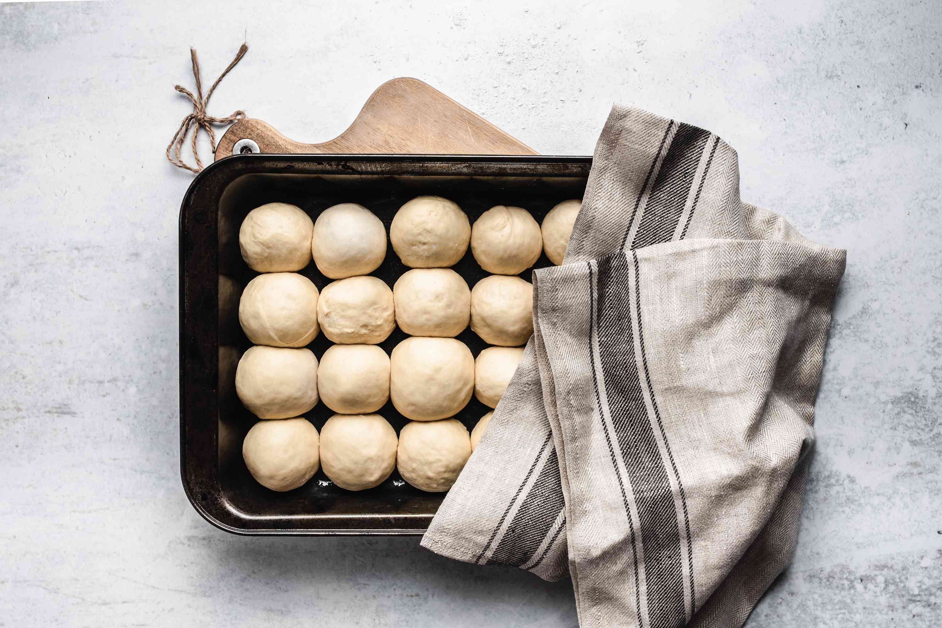 Balls of dough in baking pan covered with a towel