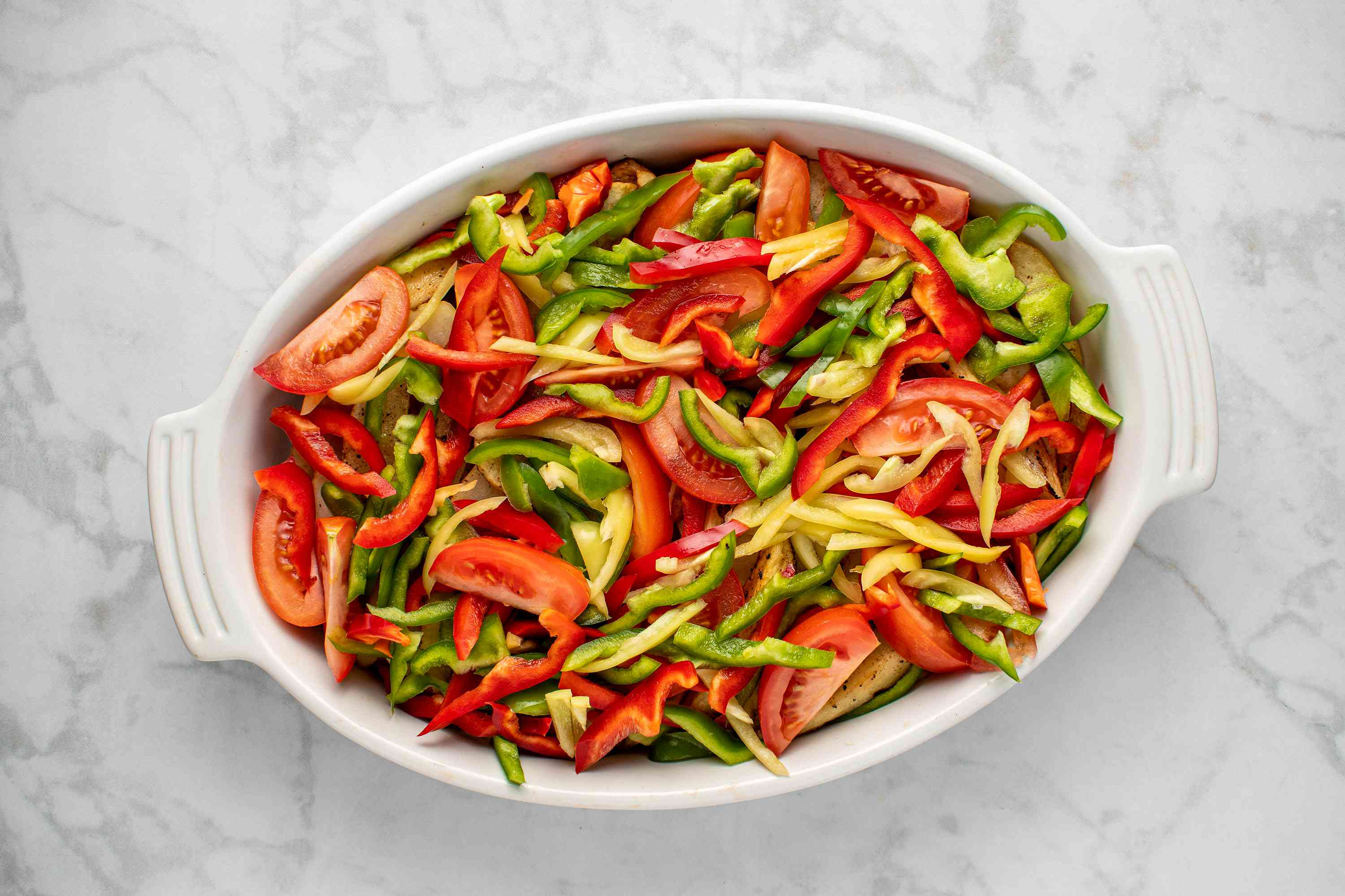 peppers and tomatoes in a baking dish