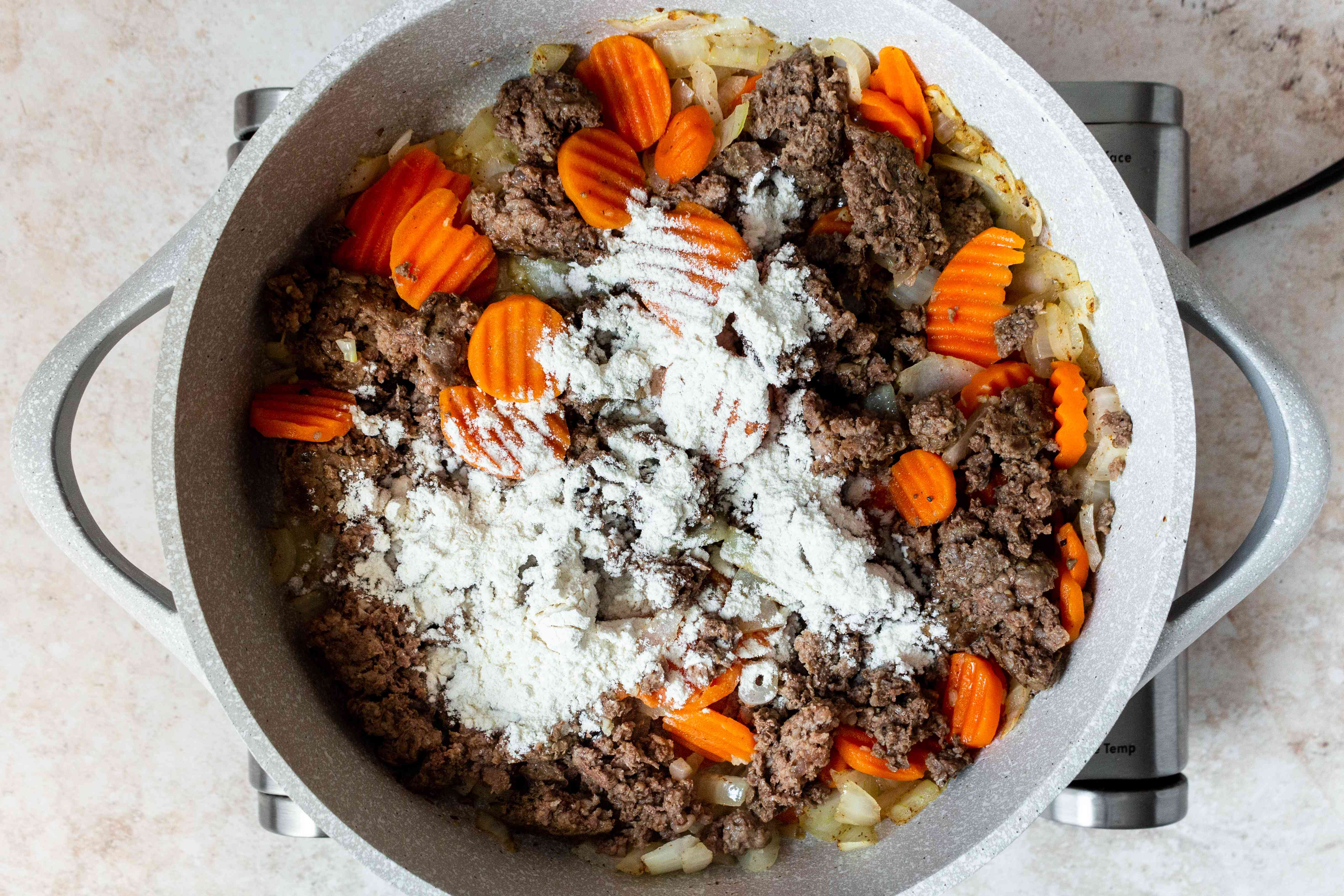 flour added to the meat and vegetable mixture in the skillet
