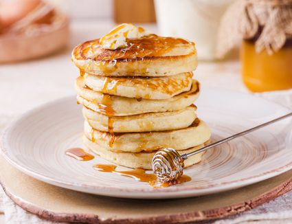 Stack of yogurt pancakes with butter and maple syrup