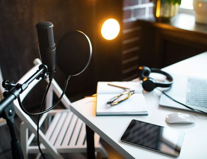 Audio studio with laptop, microphone with pop filter and headphones on white table against black wall with warm lights