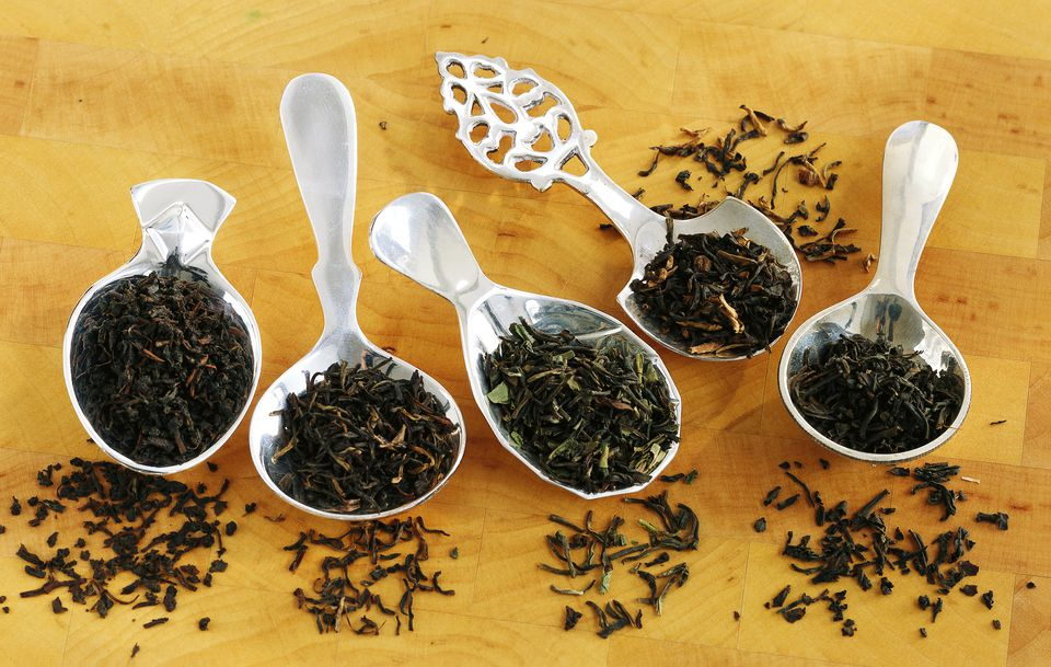 Assorted black tea leaves on tea spoons