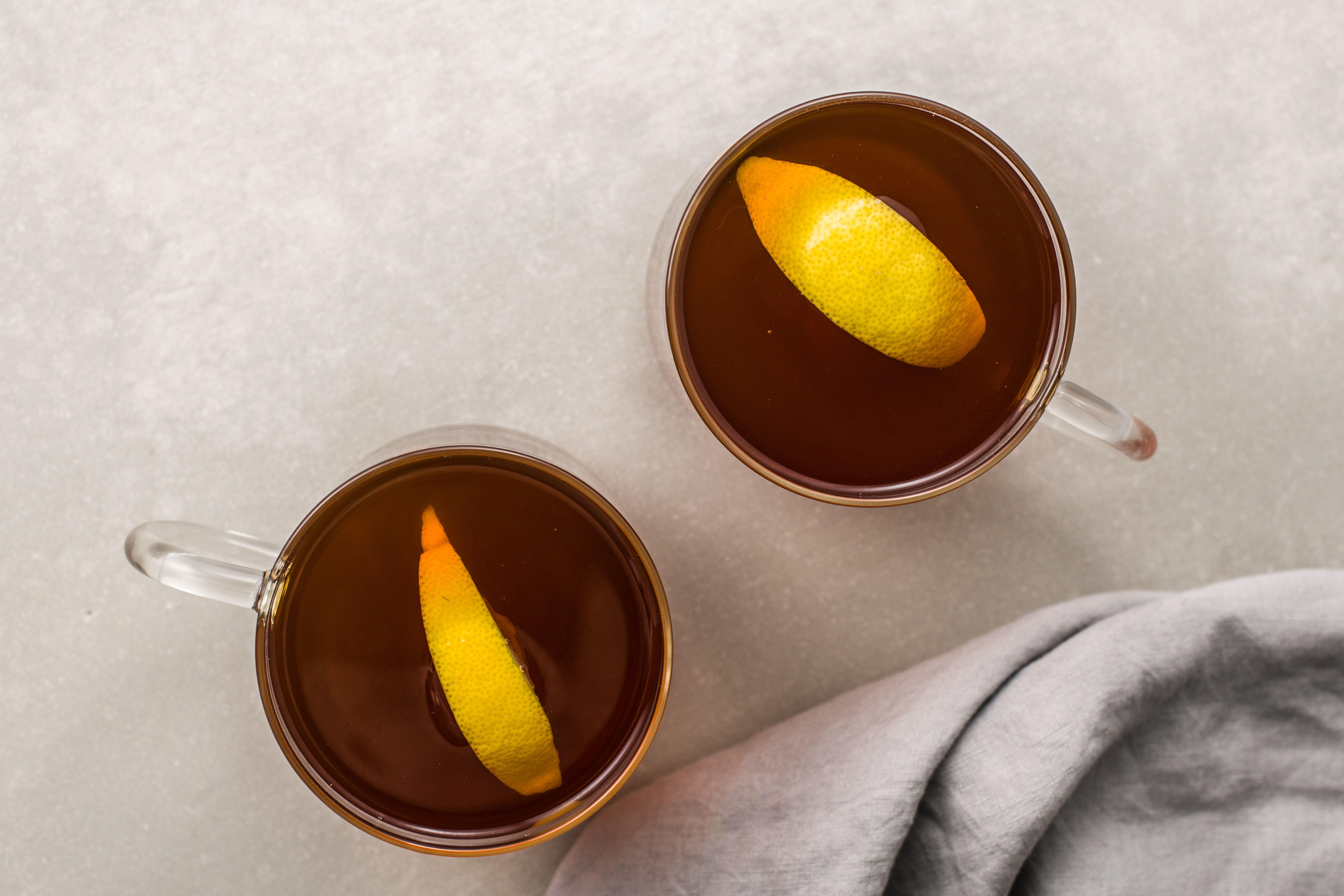 Lemon wedges in two black tea hot toddies
