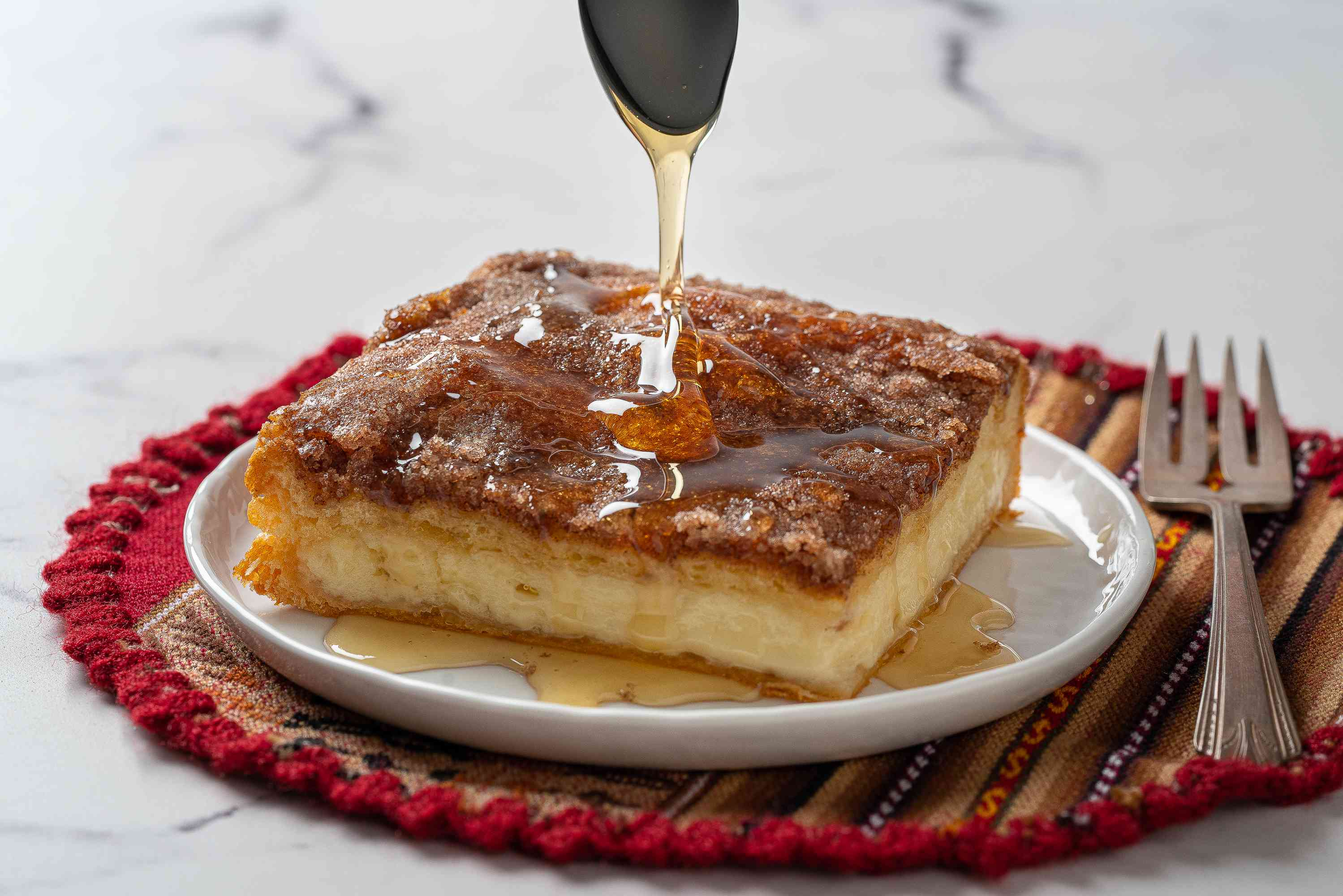 Drizzle Sopapilla Cheesecake with honey