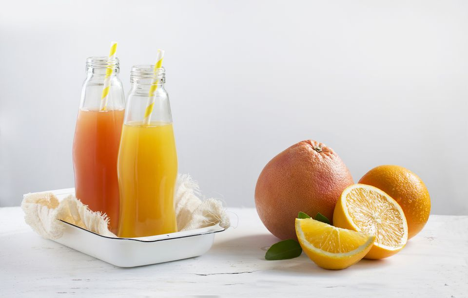 Bottles of grapefruit and oranges juice with whole fruit on a table