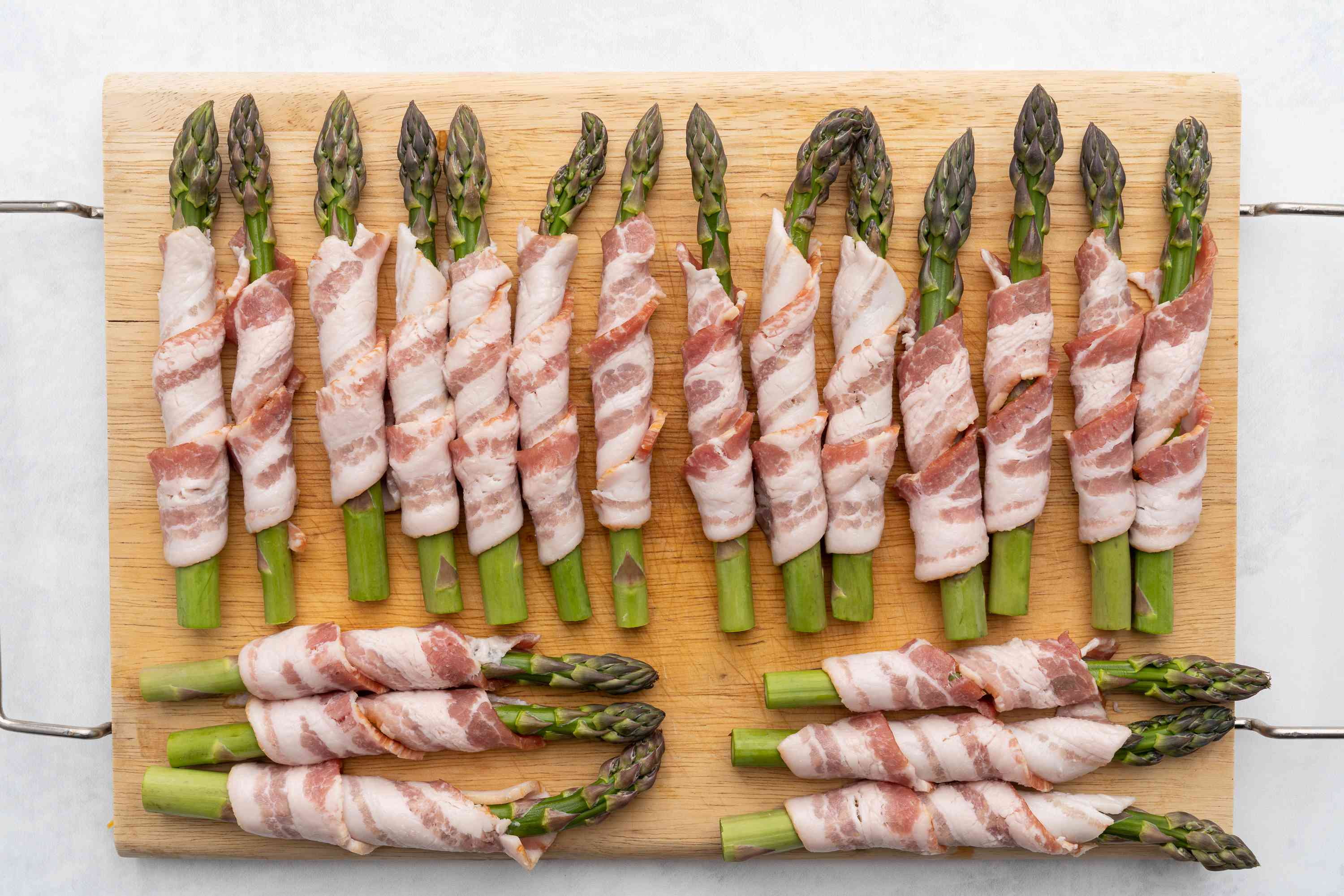 Bacon Wrapped Asparagus on a cutting board ready to be cooked