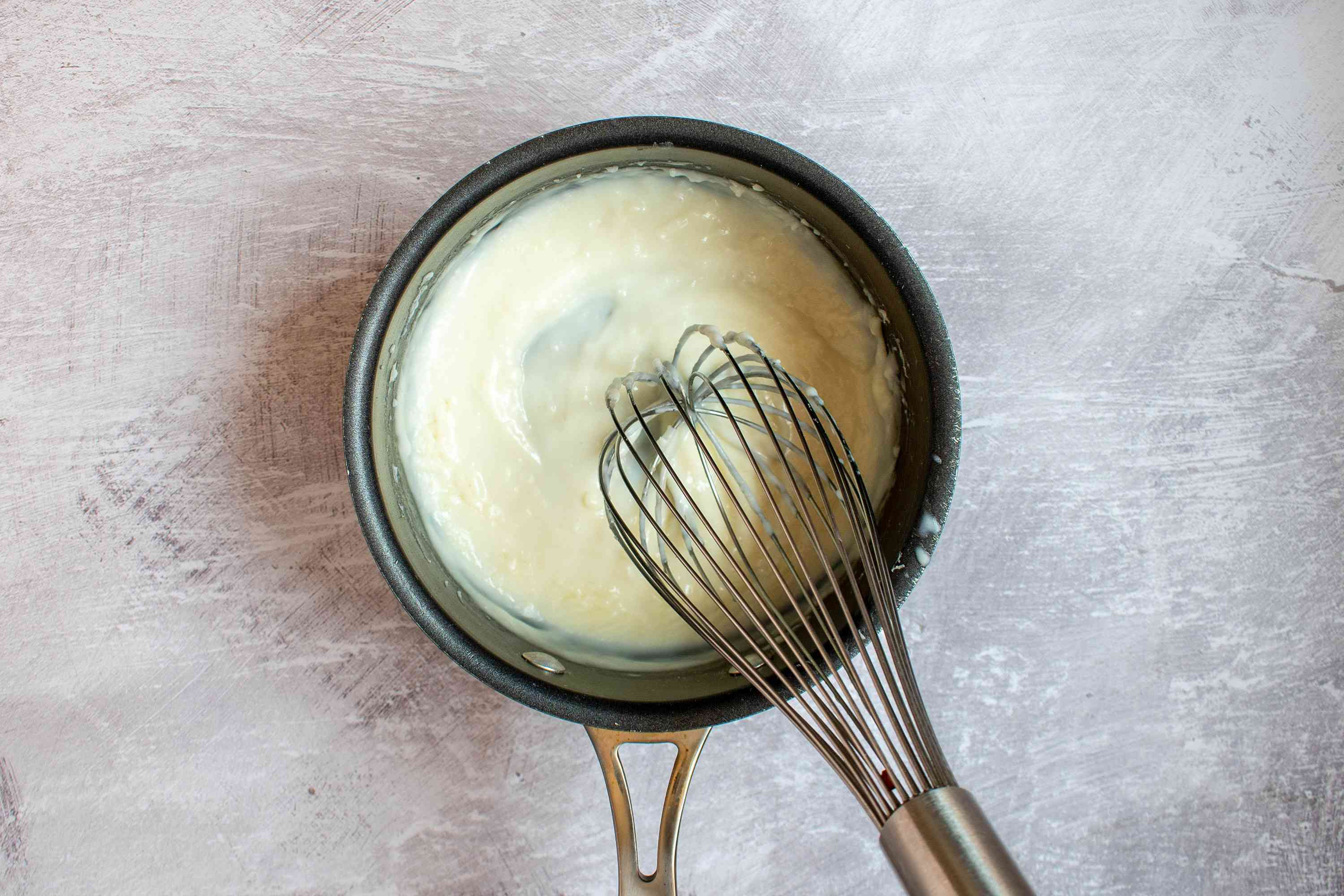 Milk whisked into butter and flour in pan