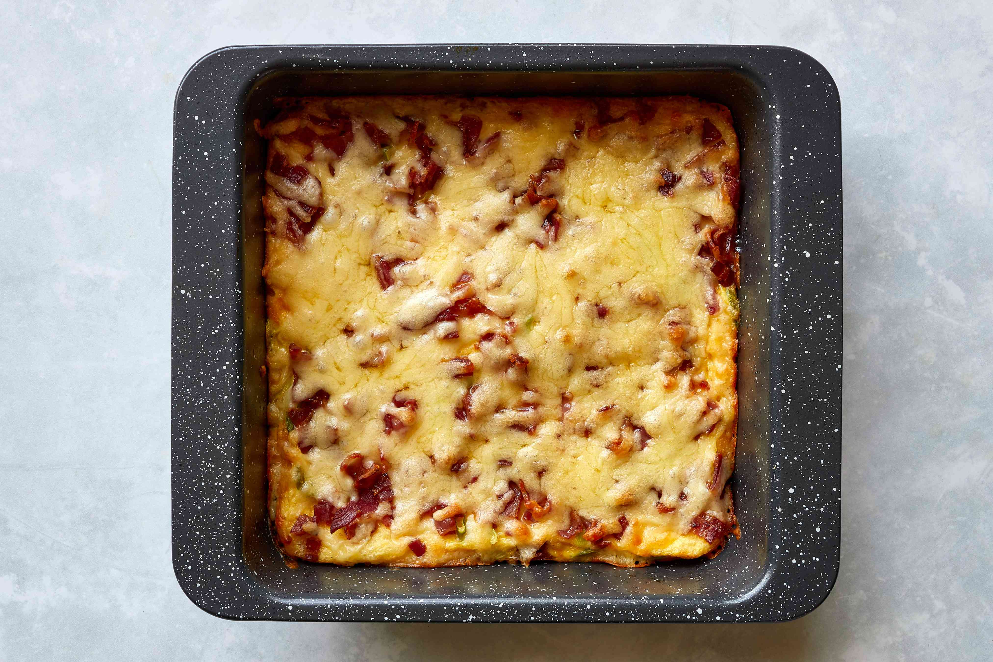 cheese on top of the bacon and egg casserole in a baking dish