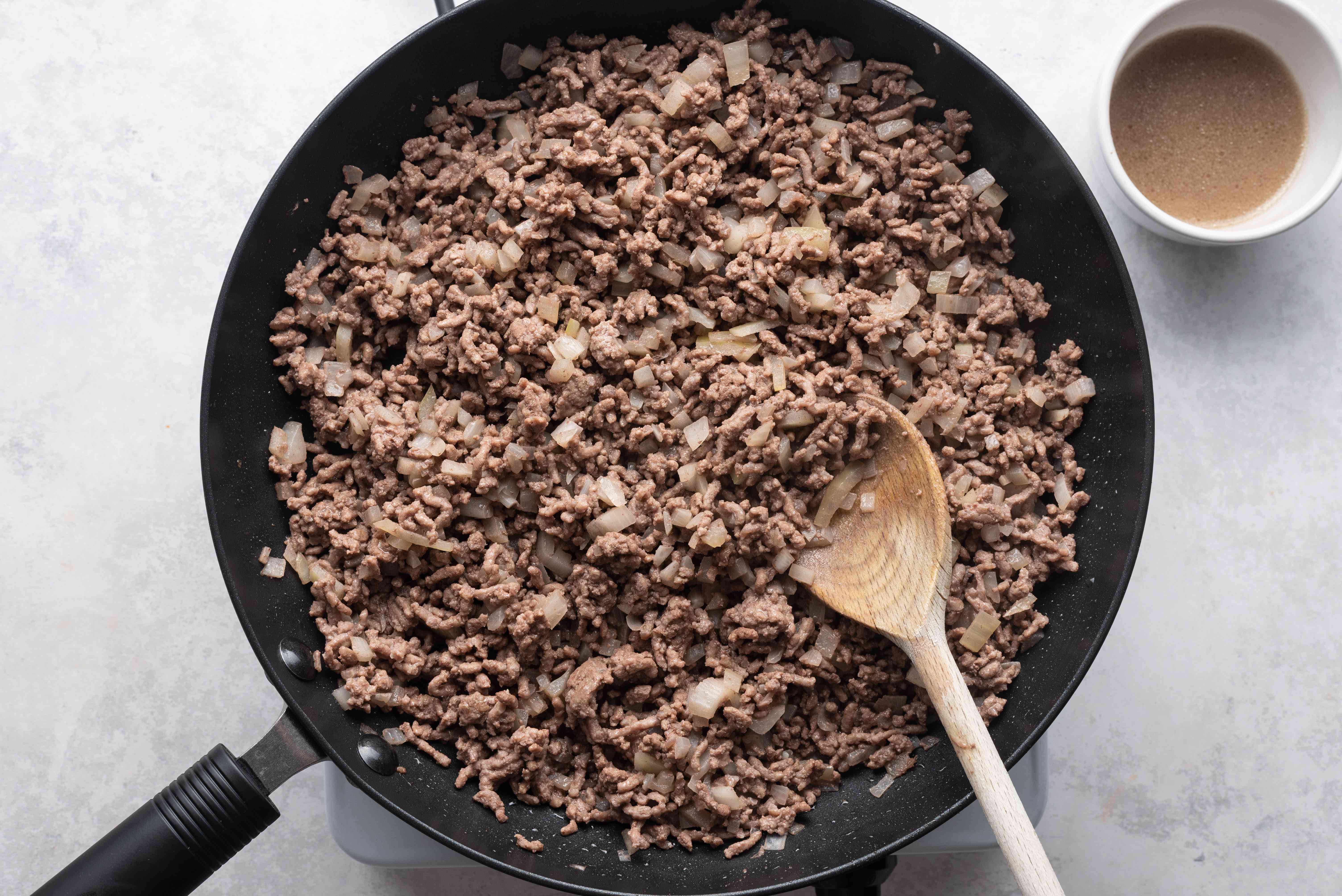 beef and onions cooking in a skillet