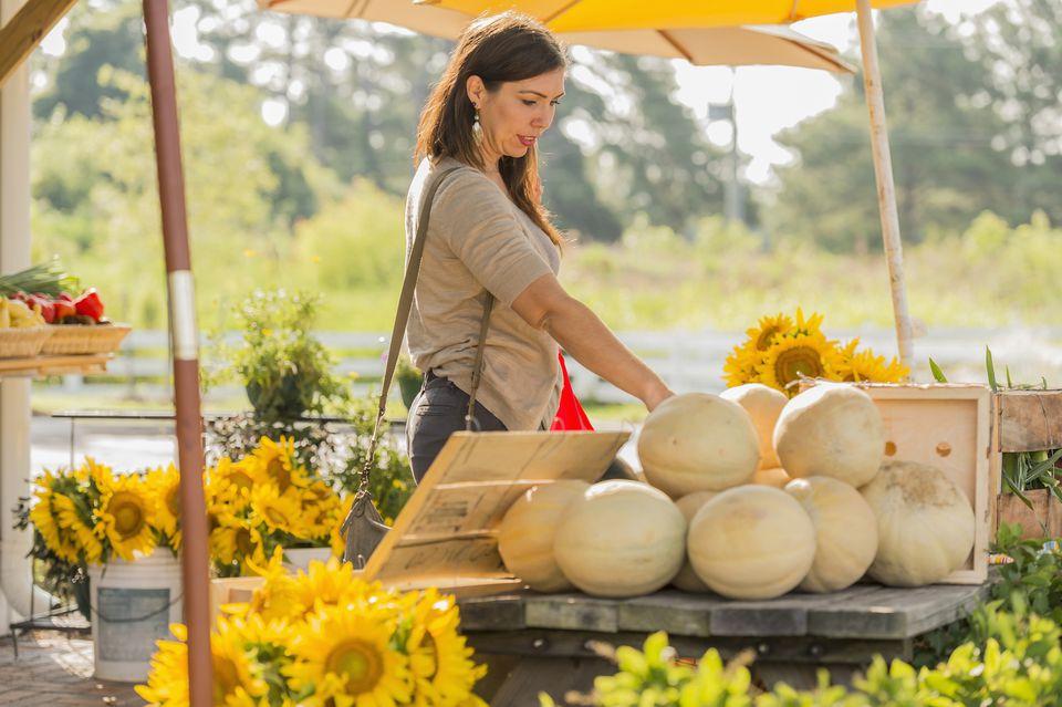 Hispanic woman browsing fruit at farmers market