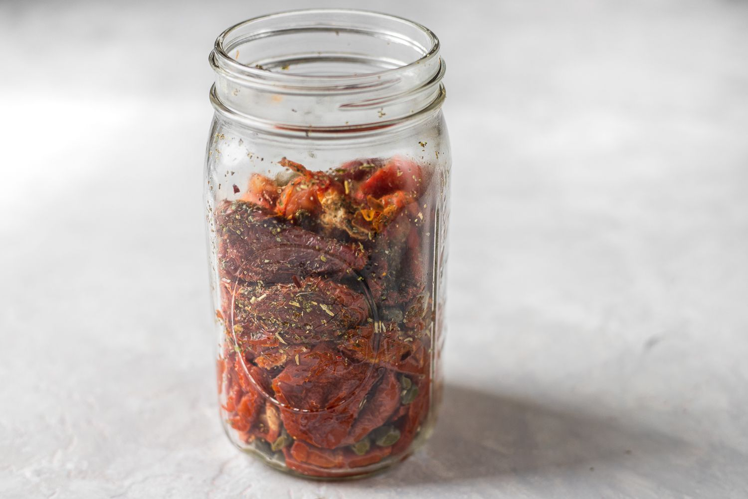 Transfer the tomatoes to the glass jar, make layers of tomatoes and seasonings