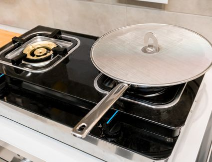 Silver metal frying pan covered with oil splatter screen on gas stove. - stock photo