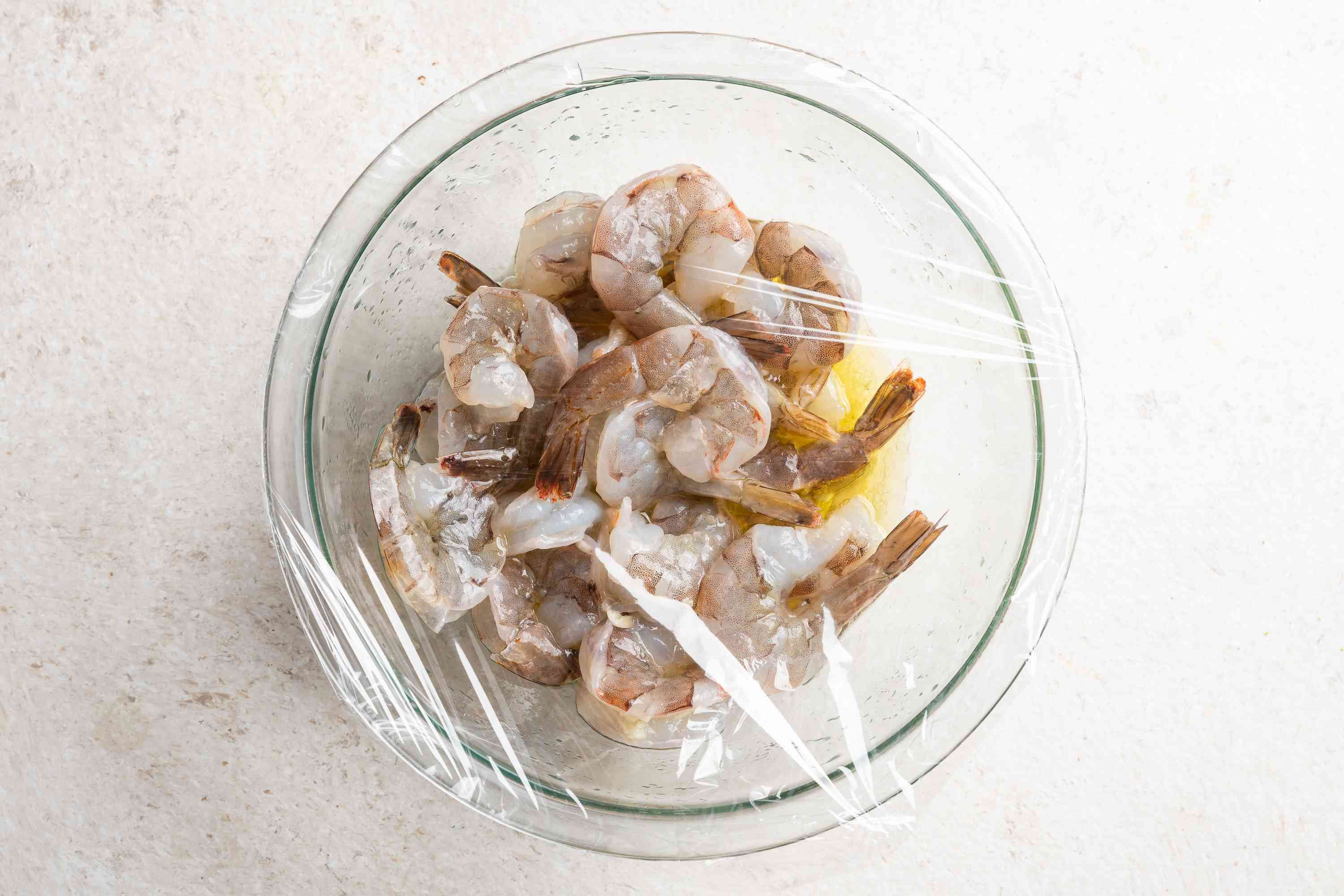 shrimp in a marinade in a bowl covered with plastic wrap