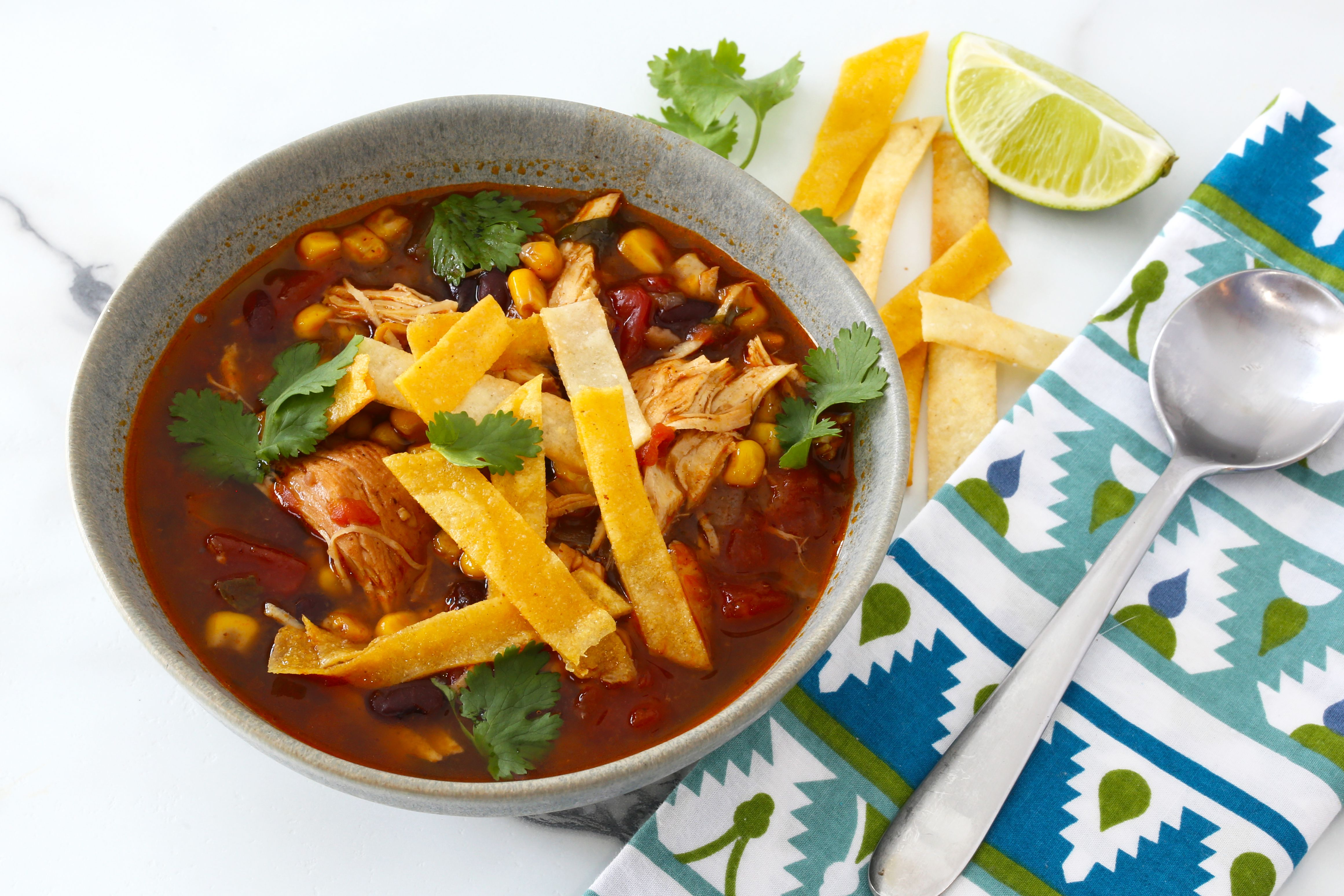 Instant Pot chicken enchilada soup in a bowl with homemade tortilla strips.