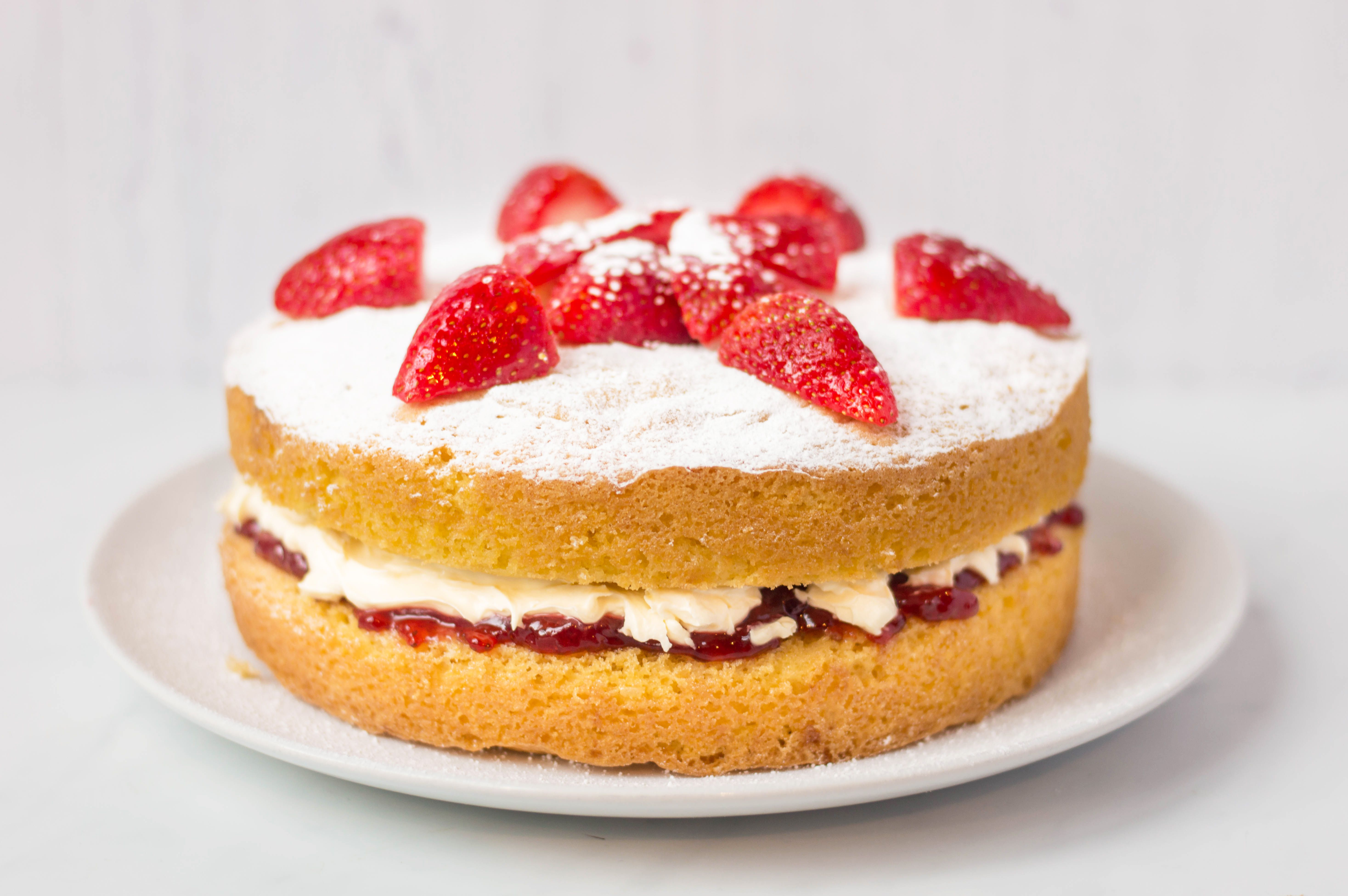Victoria sponge cake topped with confectioner's sugar and strawberries