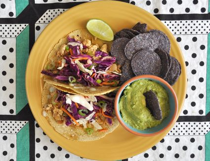 Tacos on a yellow plate on a geometric printed placemat