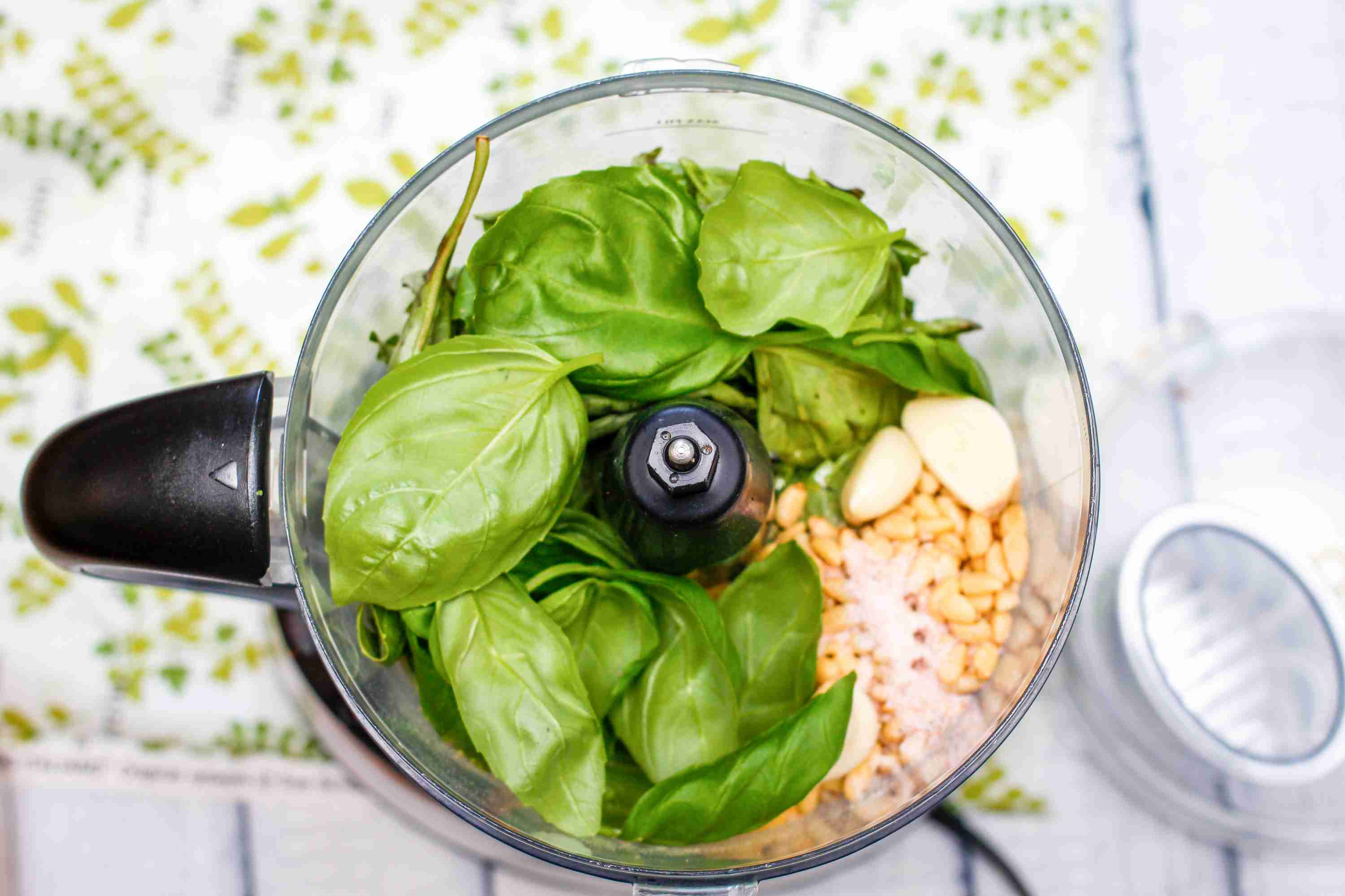 Basil, garlic, and pine nuts in a food processor for pesto