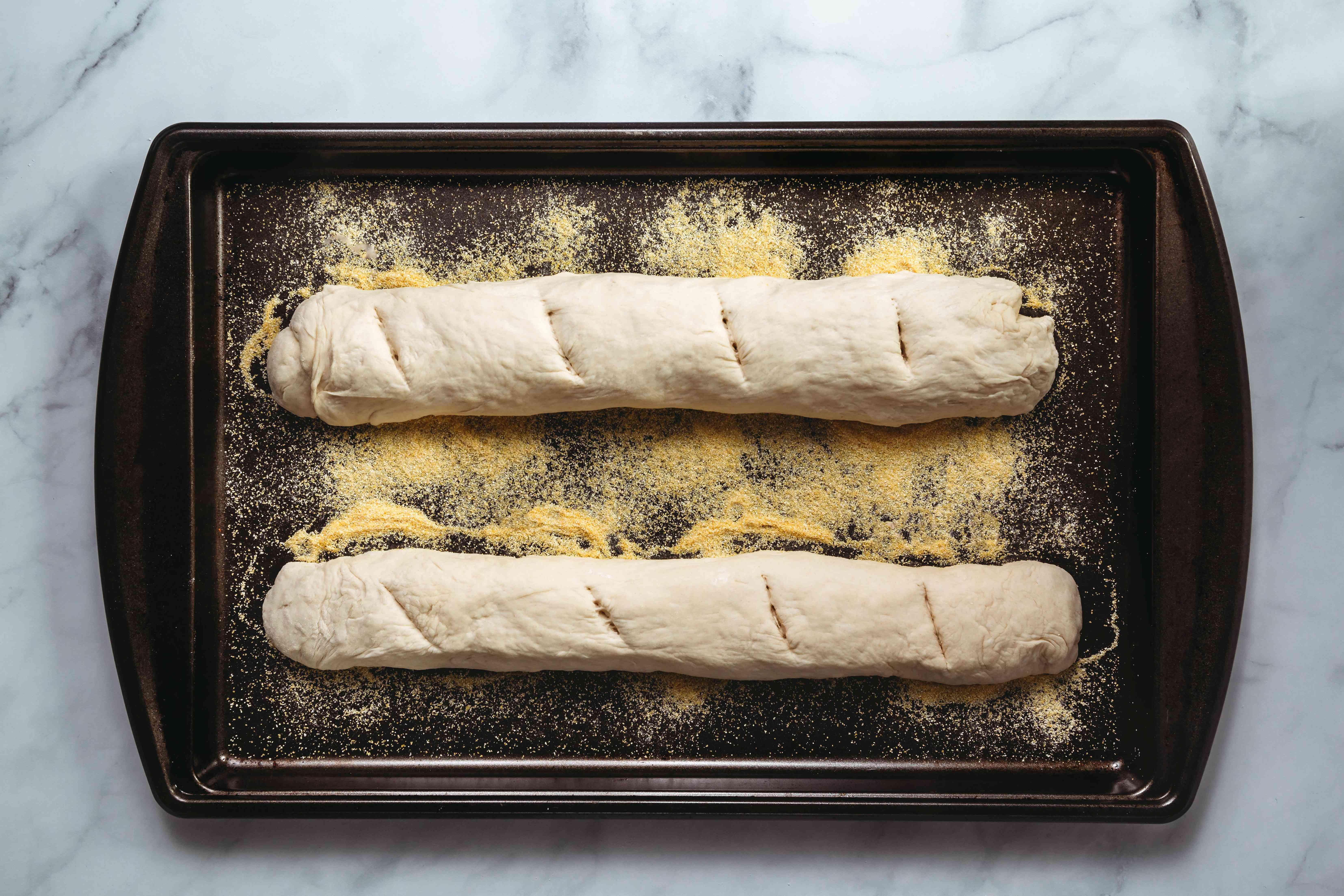 Bread dough on a baking sheet with cornmeal