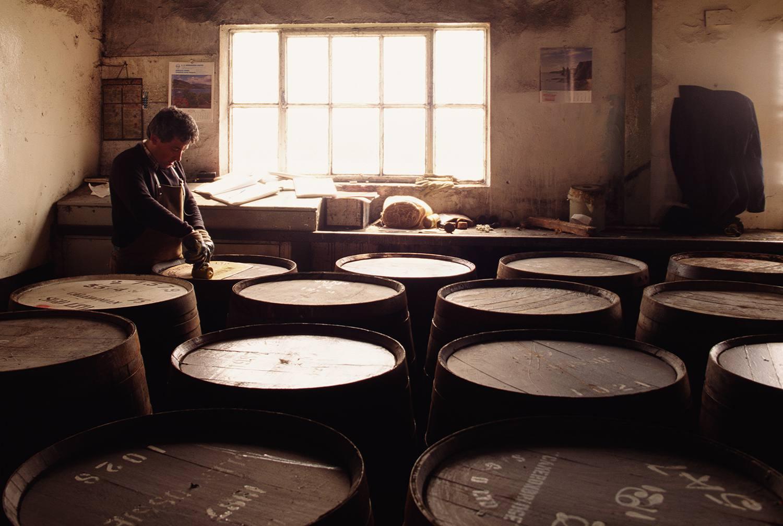 Man in barrel room of Scotch whisky distillery