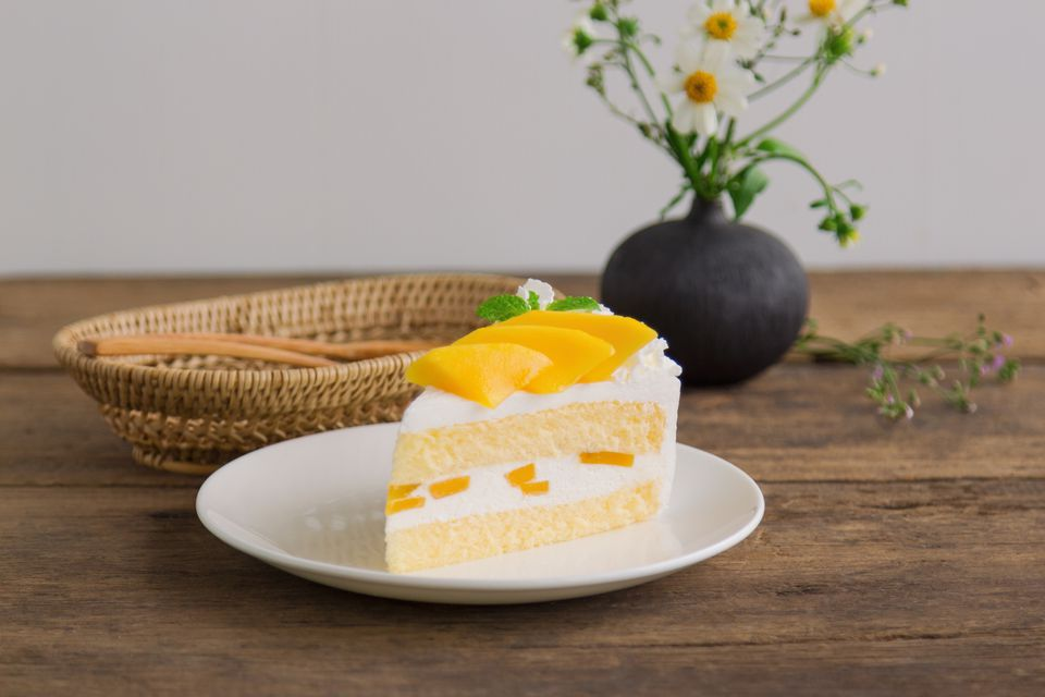 Mango Layer Cake on a white plate on a wooden table