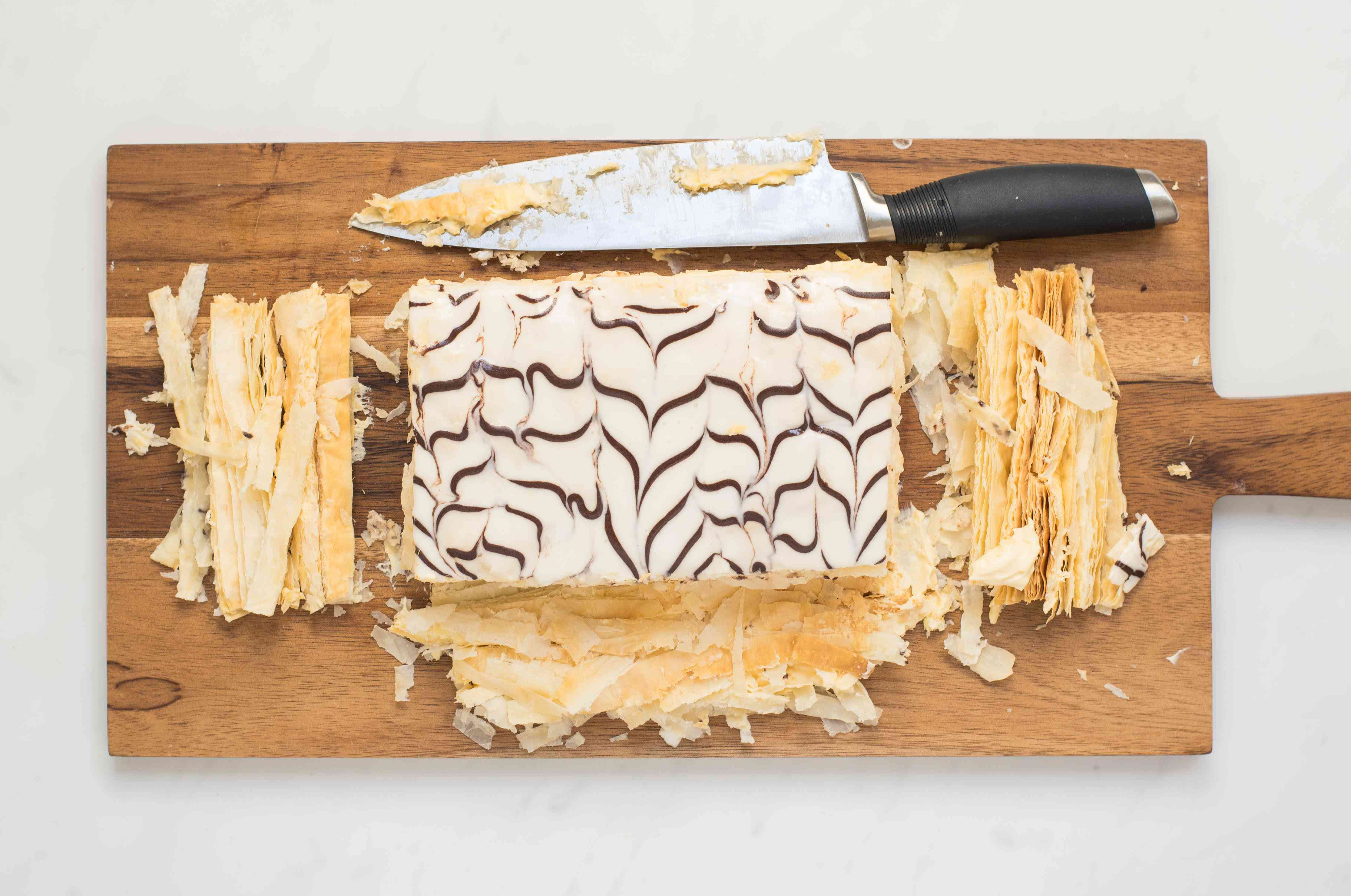 The sides of the mille-feuille are trimmed with a knife
