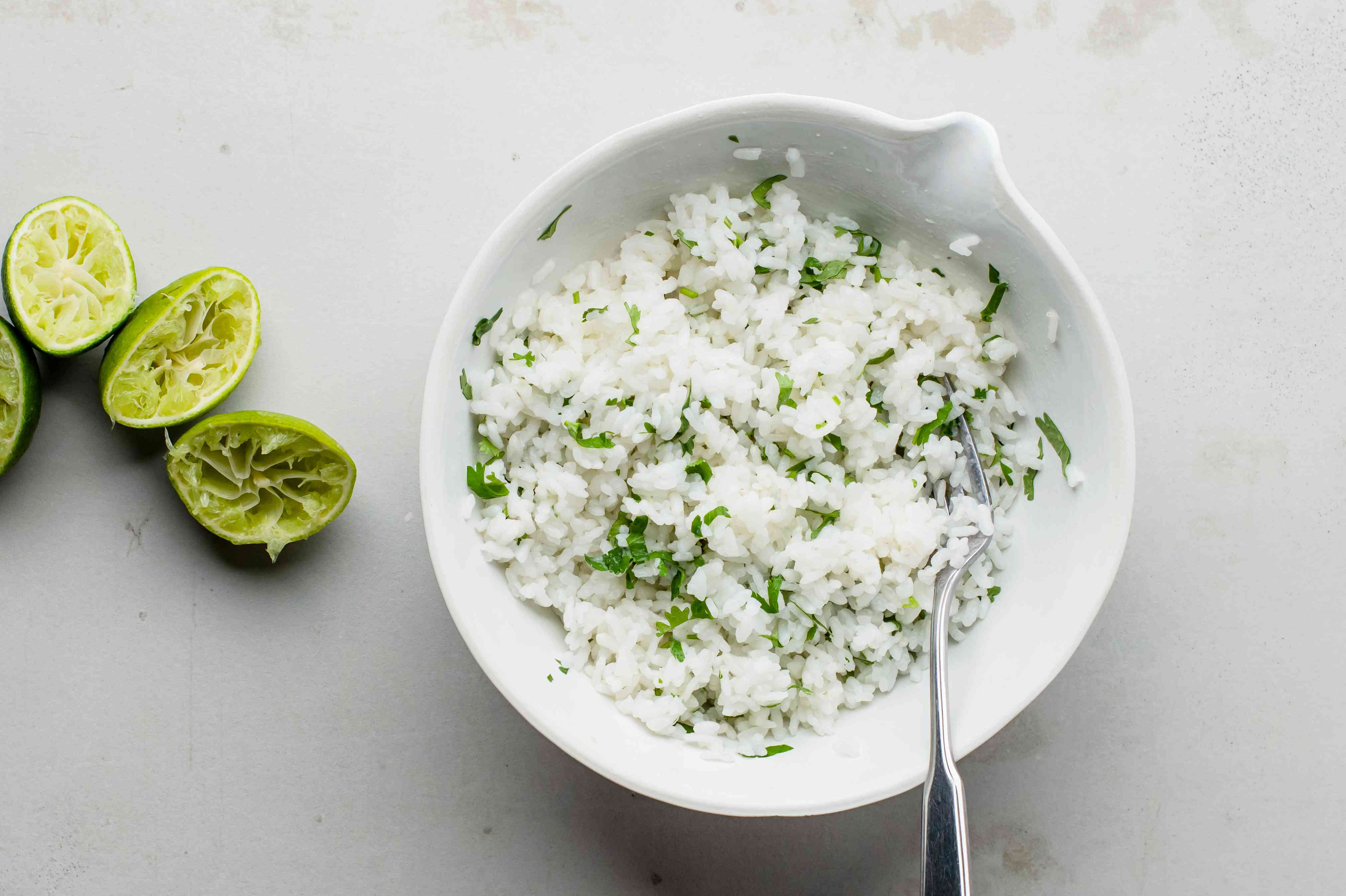 The cilantro is added to the rice and tossed in with a fork