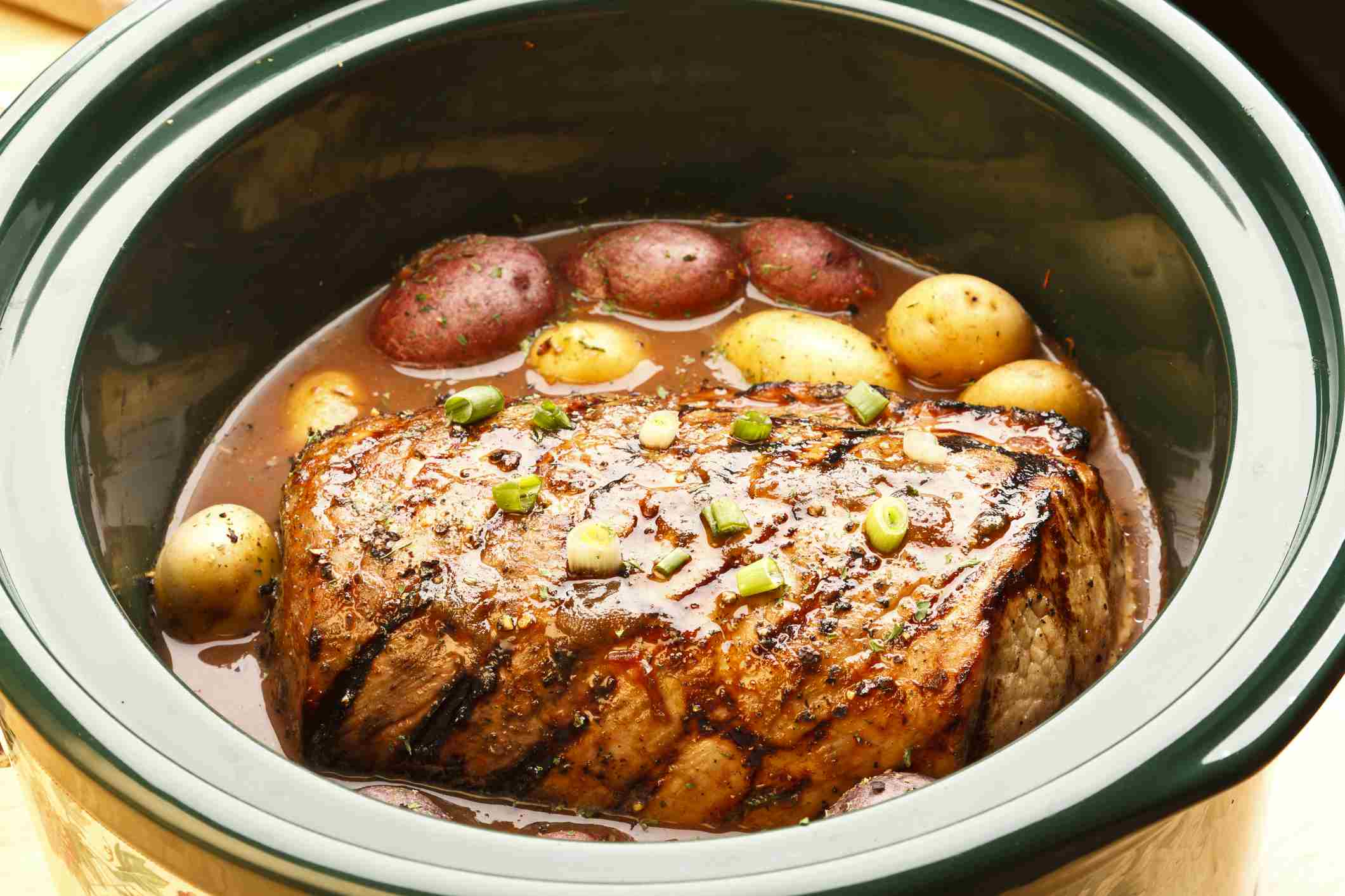 Slow Cooker filled with roast and potatoes